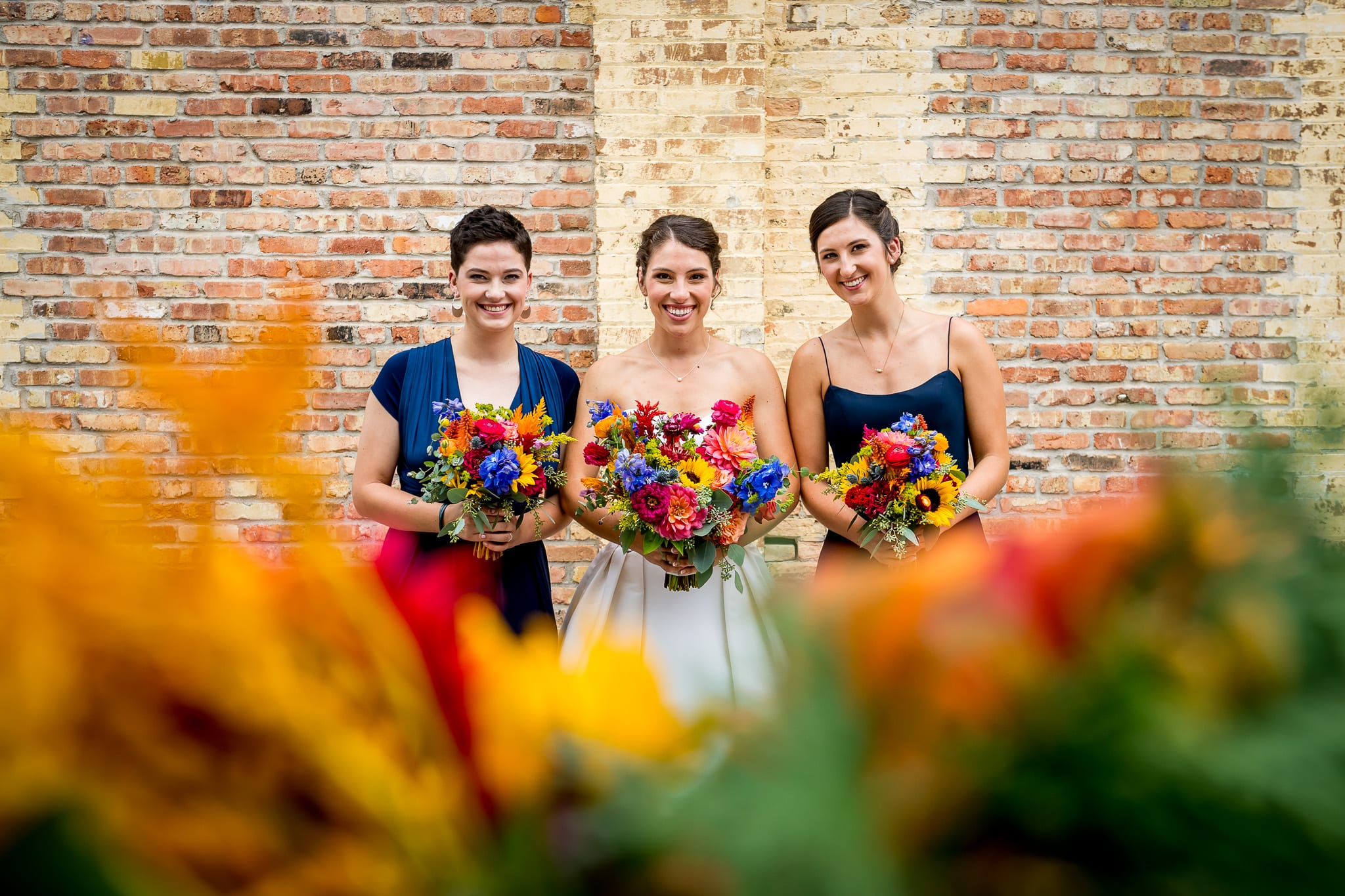 Bride and her sisters pose in front the brick wall of the Nicollet Island Pavilion with flowers surrounding them