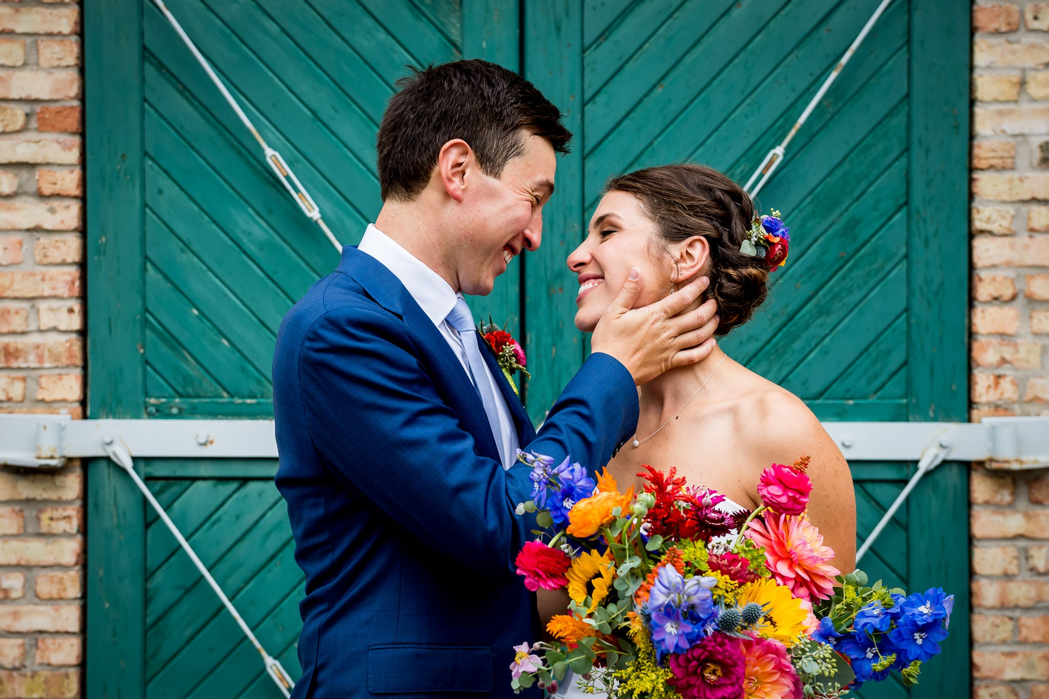 Bride and groom posing while looking at each other in front of the signature green wood and brick background at the Nicollet Island Pavilion in Minneapolis on their wedding day
