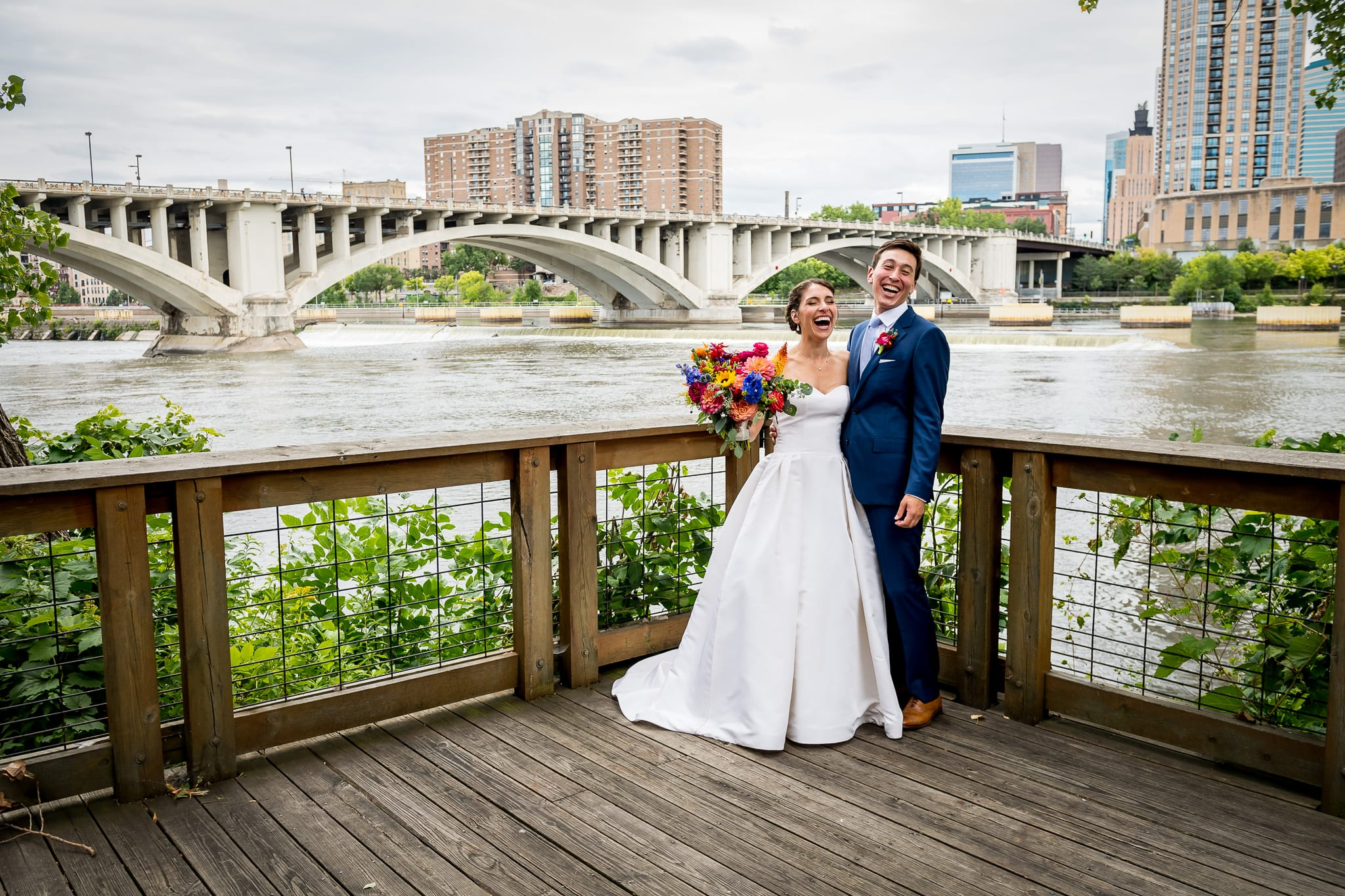 Bride and groom laughing out loud on the wooden deck at their Nicollet Island Pavilion wedding, with the Mississippi River and the Central Avenue Bridge behind them