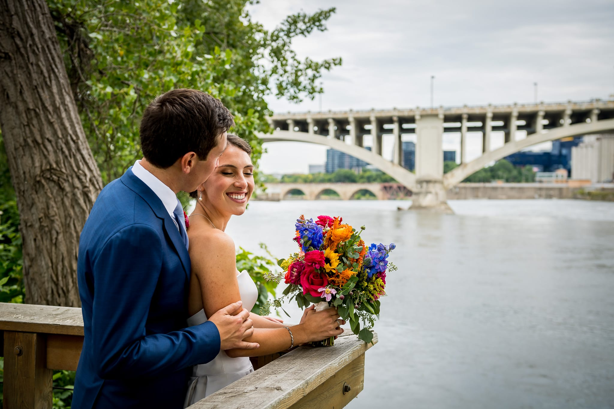 Groom whispers in his bride's ear as they overlook the Mississippi River with the Central Avenue Bridge and Minneapolis in the background on their wedding day