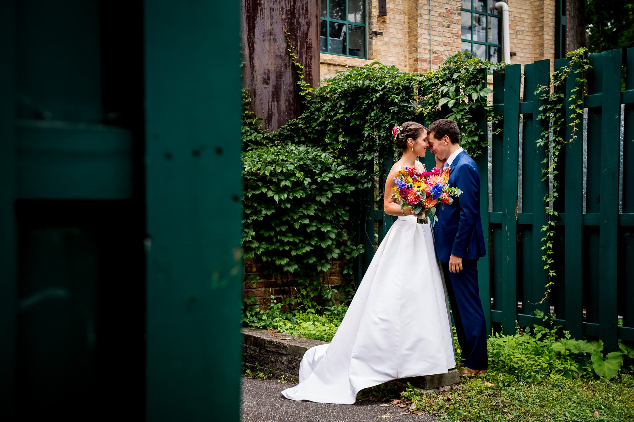 Bride and groom near the ivy and green fences in the back of the Nicollet Island Pavilion on their wedding day