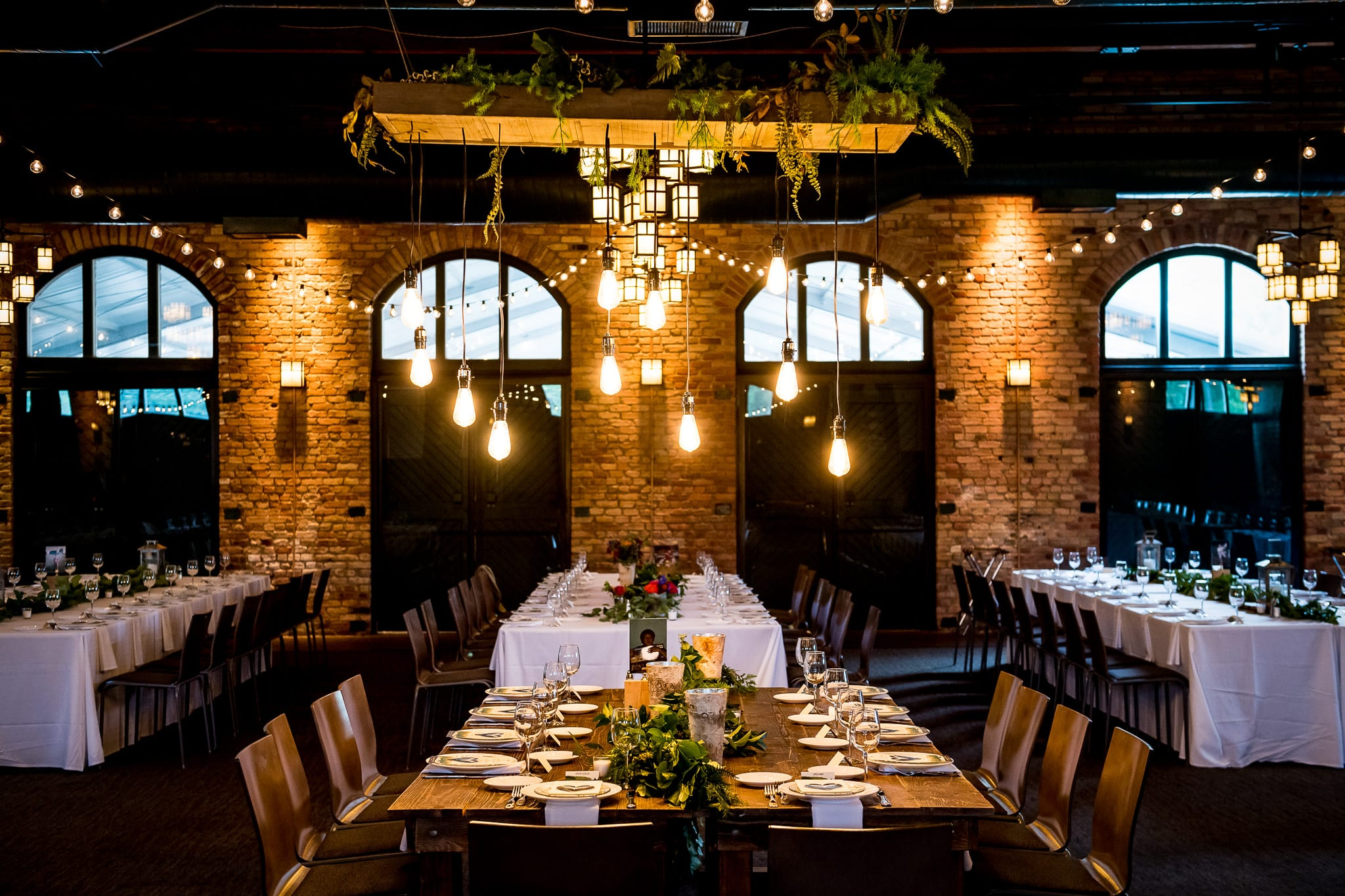 The head table with bright and modern hanging lights at a Nicollet Island Pavilion wedding