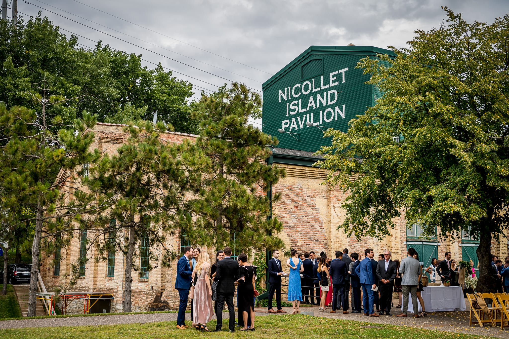 Nicollet Island Pavilion signage and guests arriving prior to an outdoor summer wedding ceremony