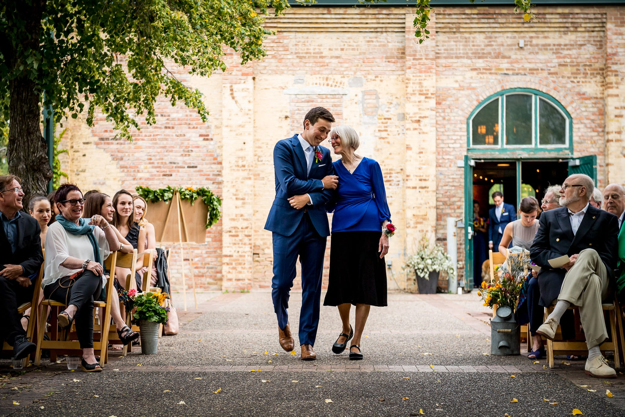 Groom and his mother walk dawn the isle during and outdoor wedding at the Nicollet Island Pavilion