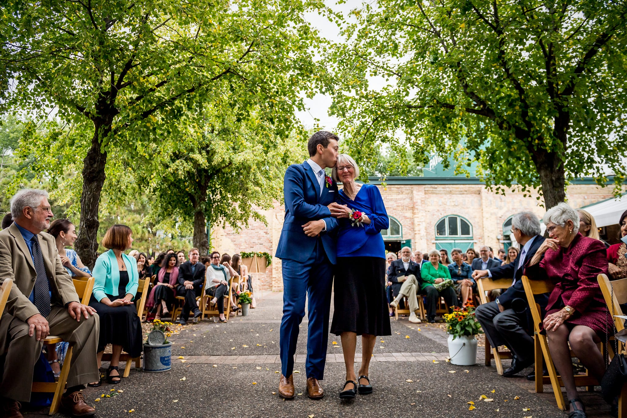 Groom kisses his mother on the temple while she walks him down the isle with a giant smile on her face