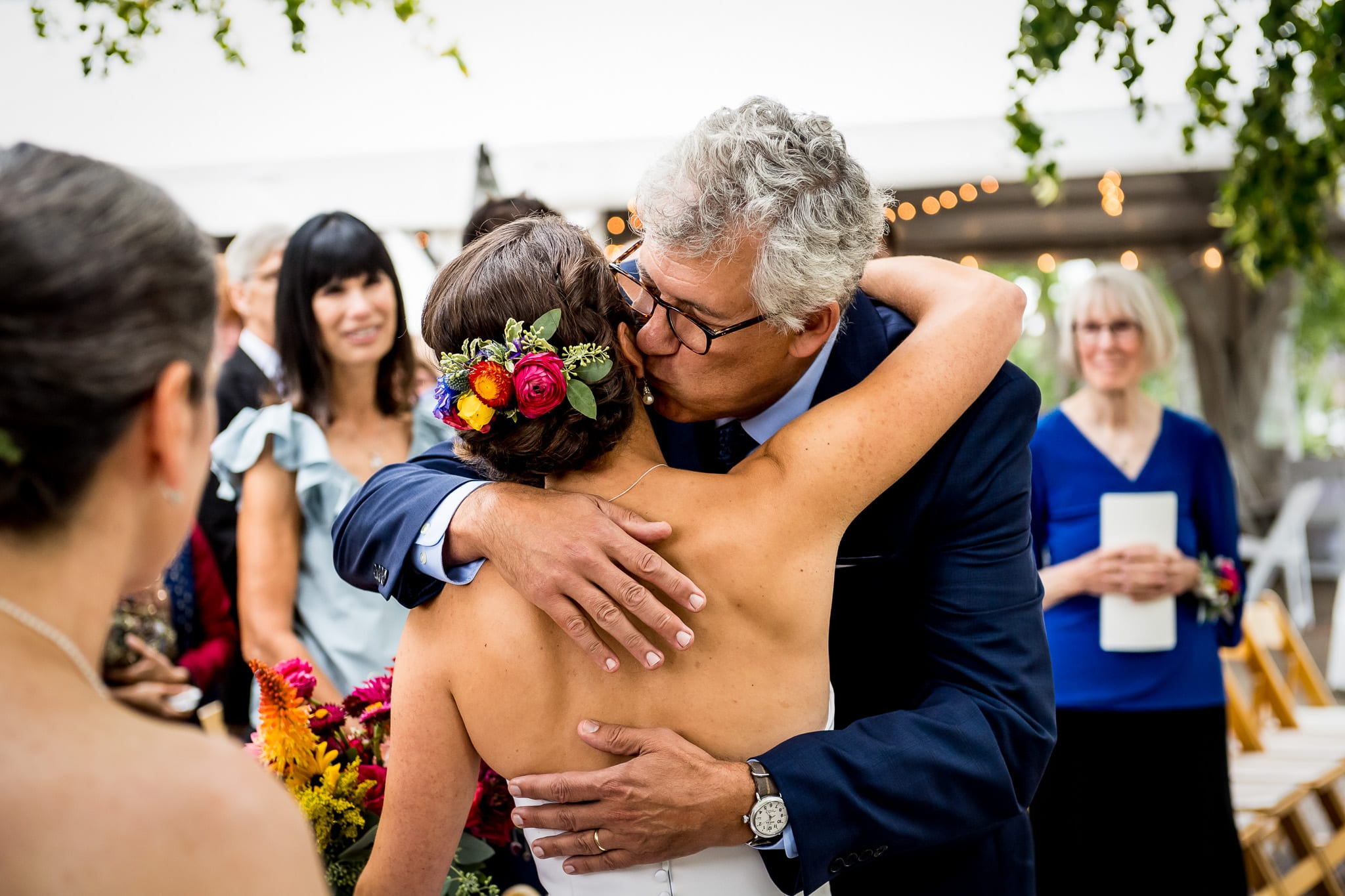 Father of the bride hugs his daughter as he hands her off to be married