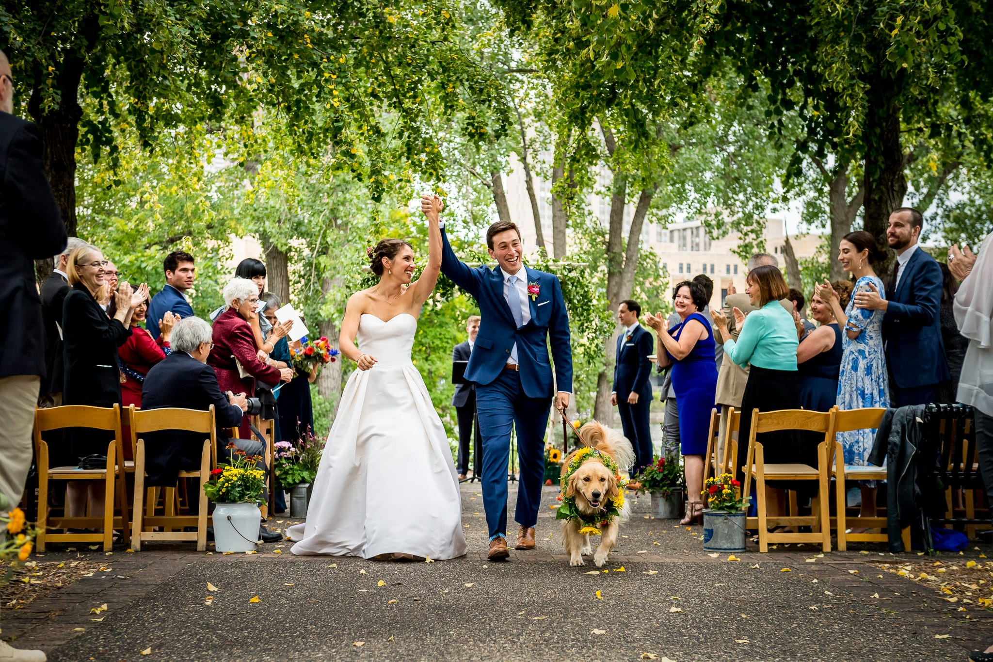 Bride and groom are announced as a married couple as they walk back out the isle, with their arms high in the air, and with their golden retriever ring bearer, during their wedding ceremony at the Nicollet Island Pavilion