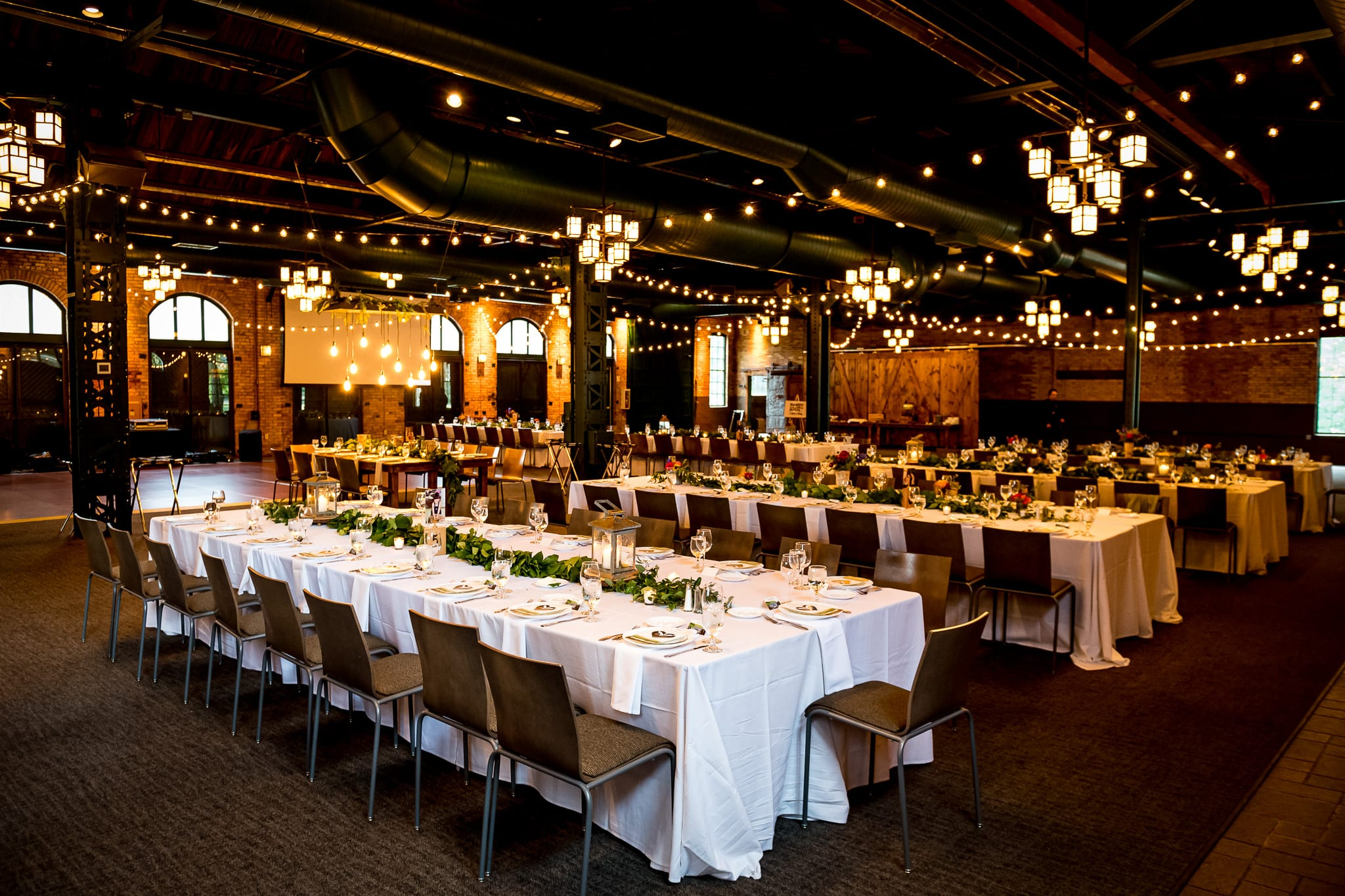 Wide shot of the Nicollet Island Pavilion all set up for a wedding reception before the guests have been seated