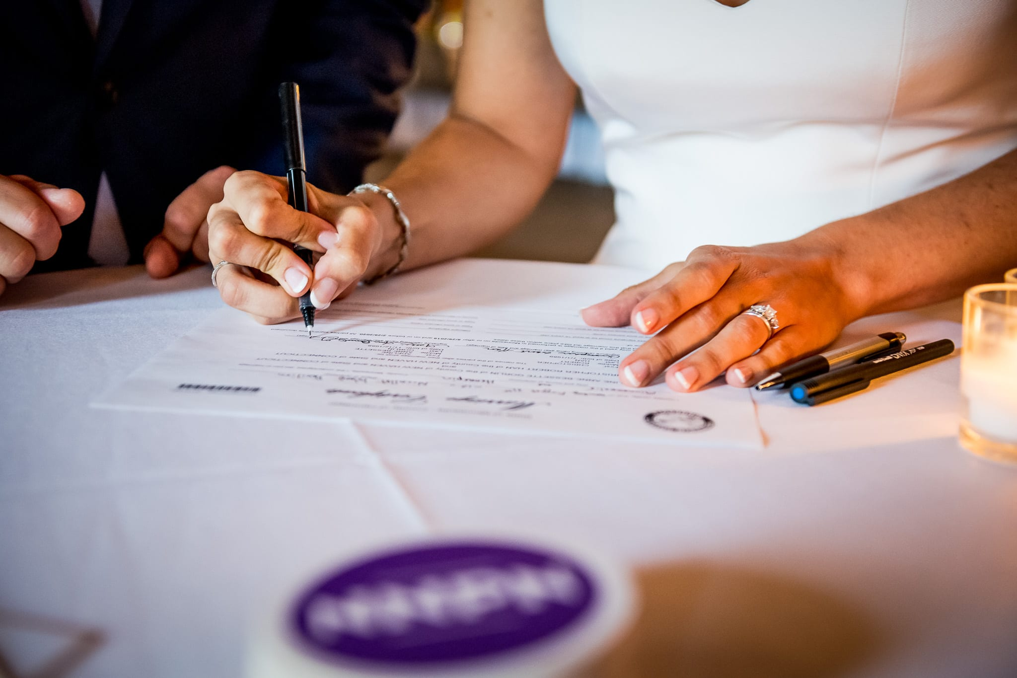 Bride signs her wedding certificate at the Nicollet Island Pavilion