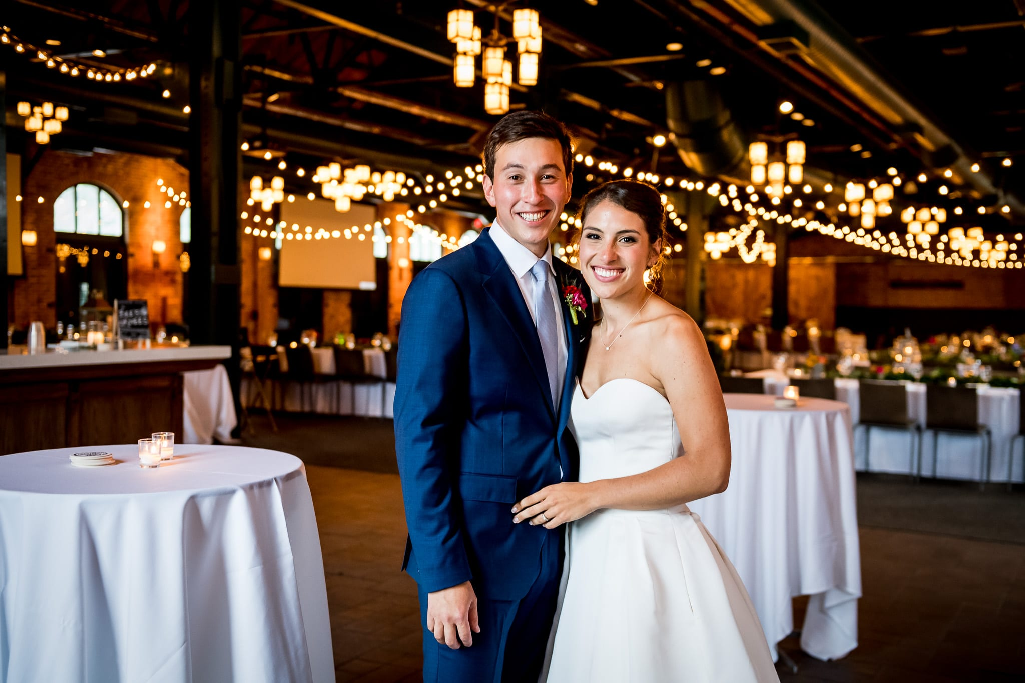 Bride and groom smiling for the camera inside the Nicollet Island Pavilion