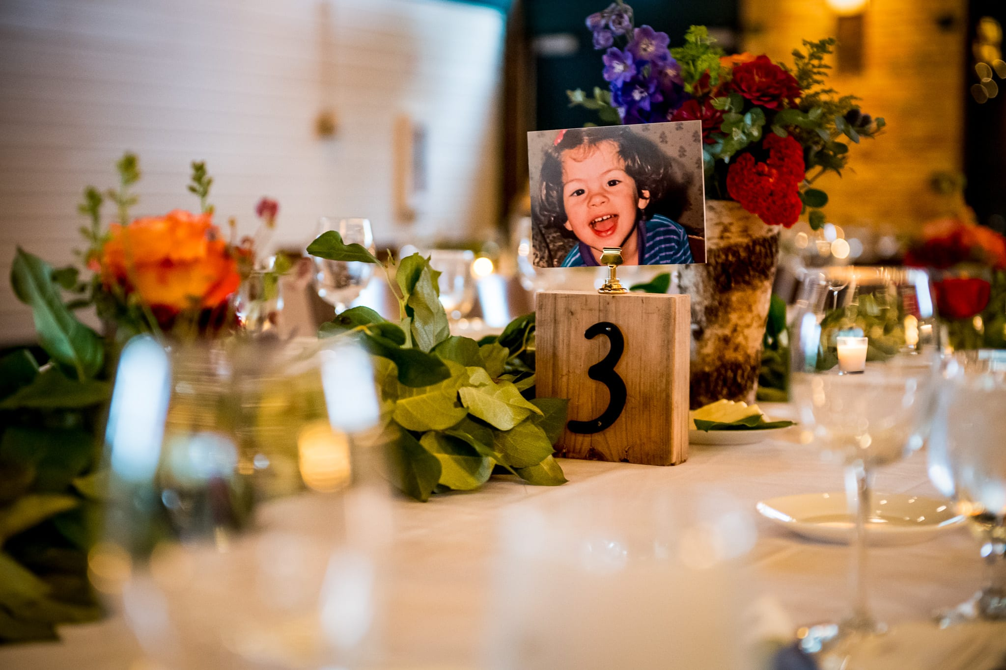 Unique table setting with table number centerpiece with photos of the bride when she was a little kid