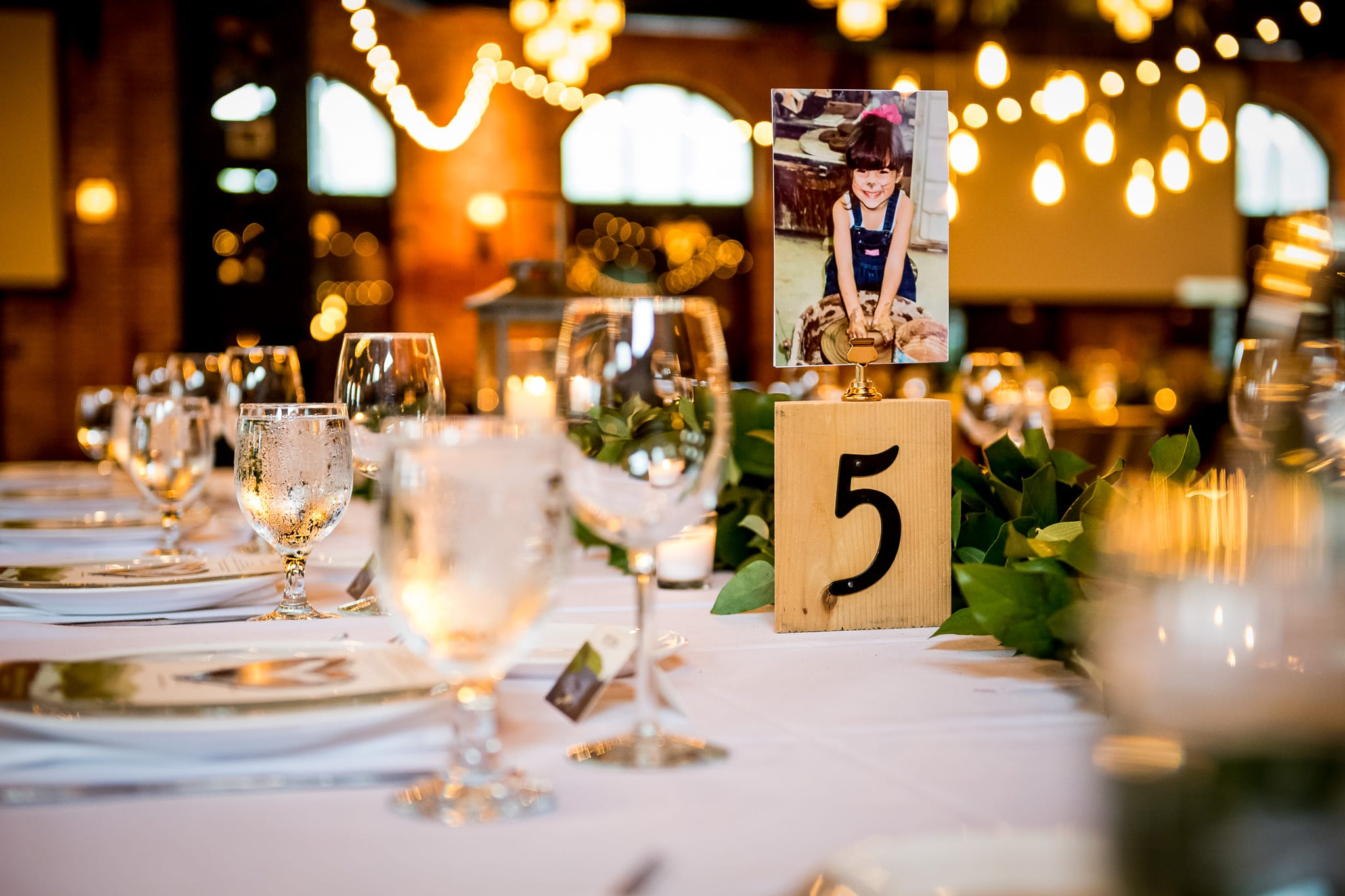 Table setting and view of the space inside the Nicollet Island Pavilion during a wedding reception