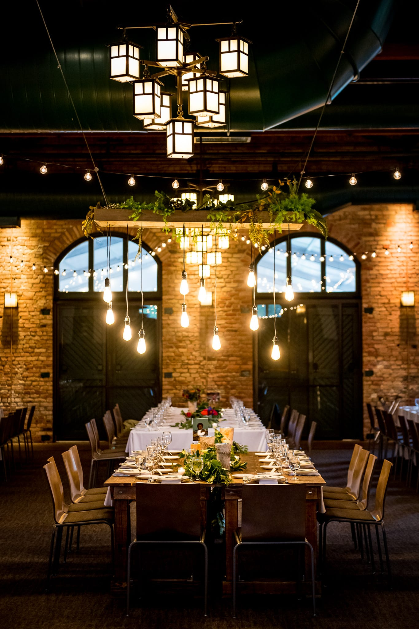 Tall view of the head table and the inside of the Nicollet Island Pavilion during a summer wedding reception