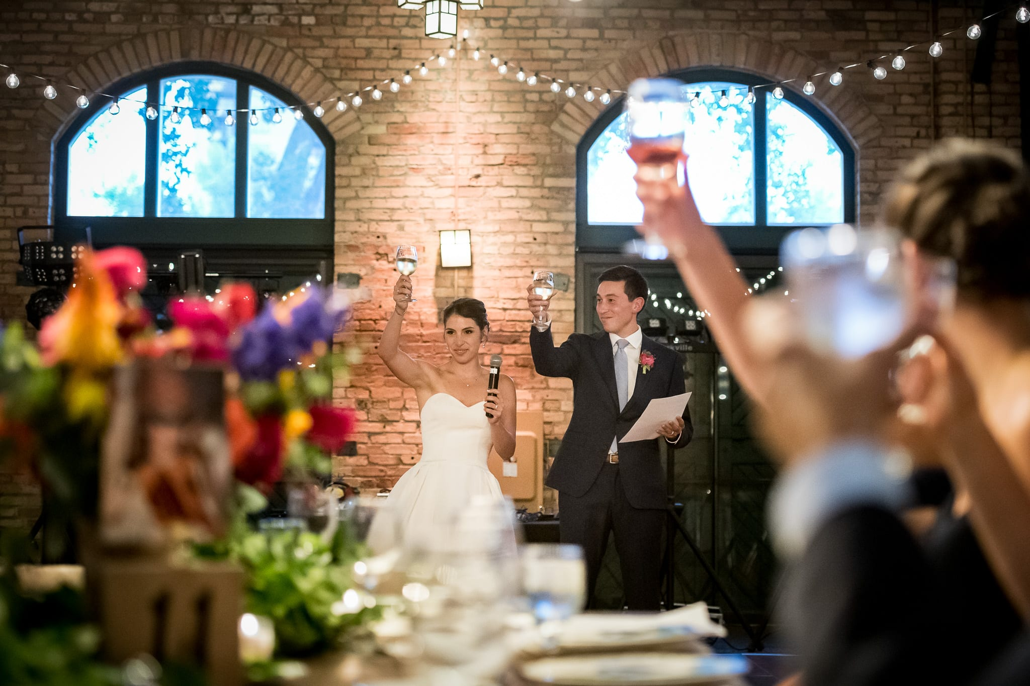Bride and groom toast their guests with arms raised