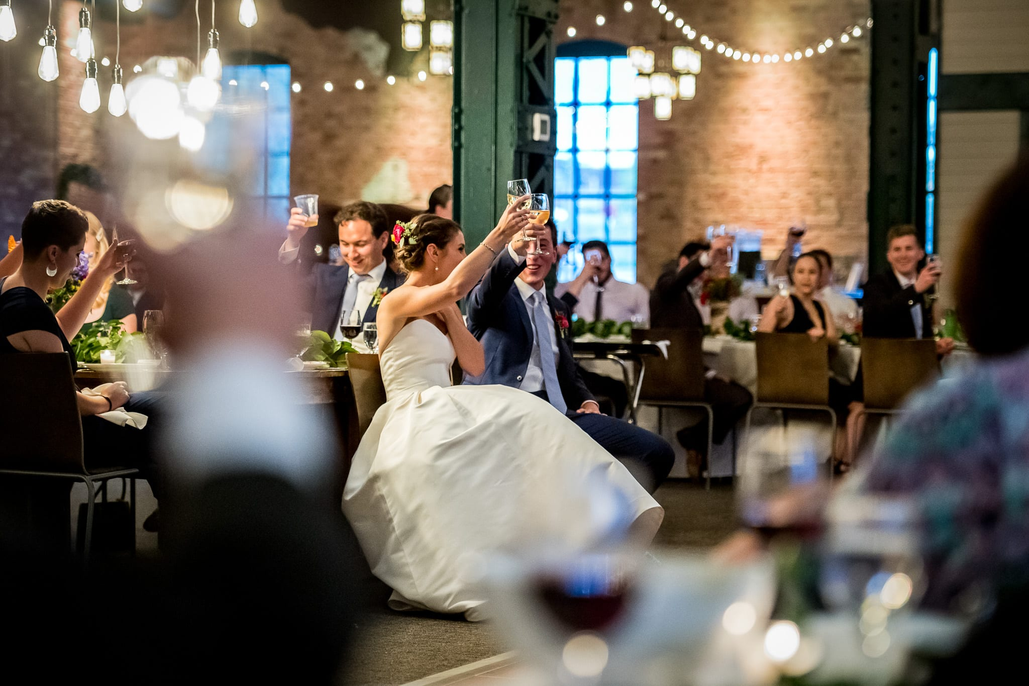 Many arms raised to cheers showing the large area inside of the Nicollet Island Pavilion during a summer wedding reception