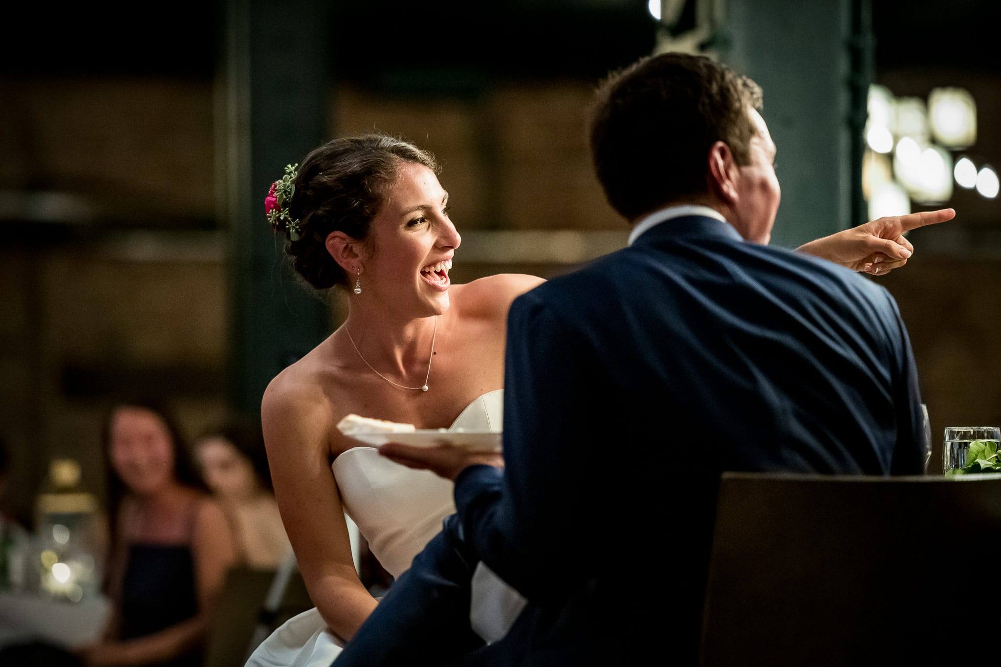 Bride laughing and pointing during wedding speech