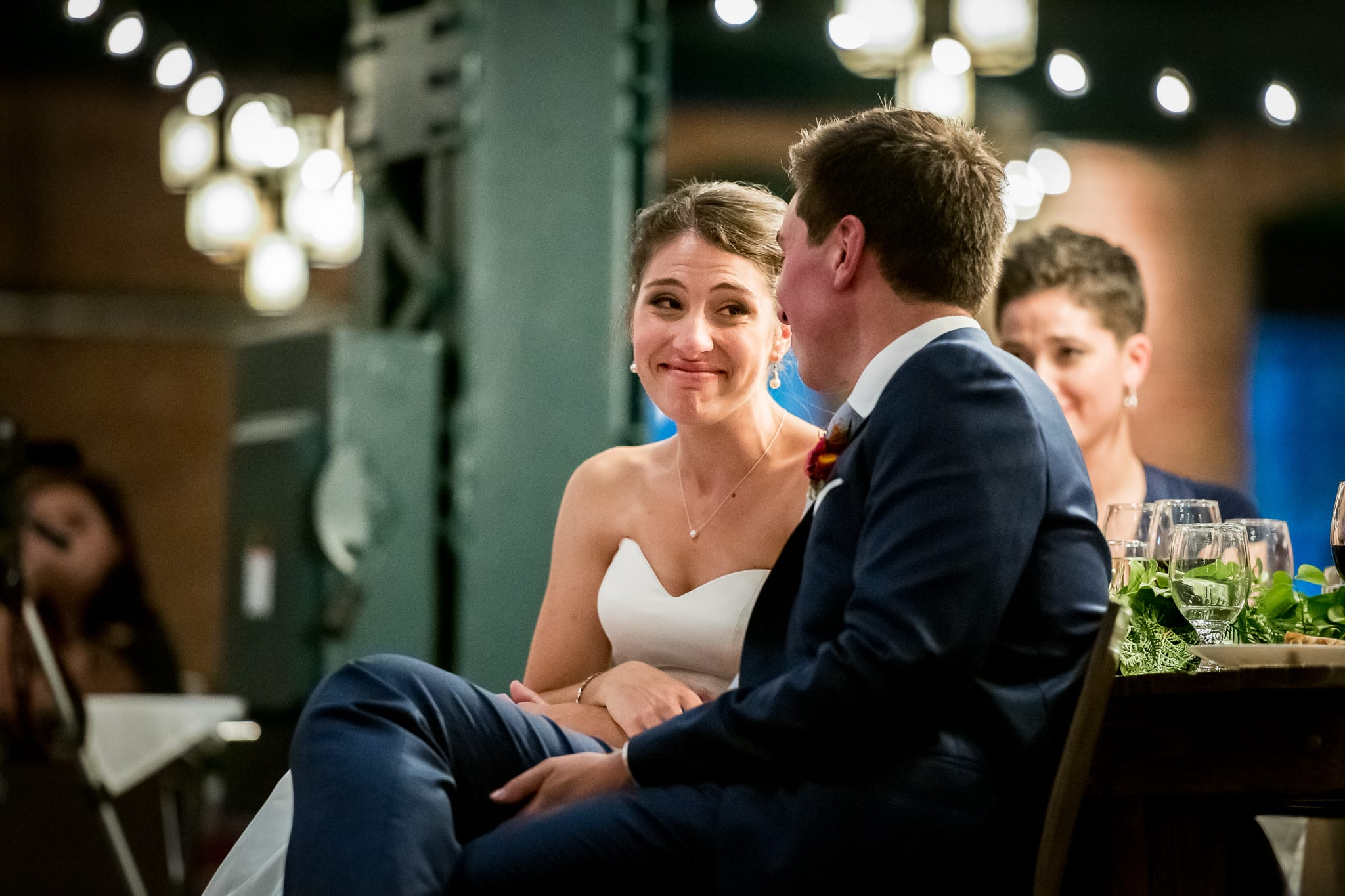 Bride looks at groom with tear filled eyes during their wedding reception inside the Nicollet Island Pavilion