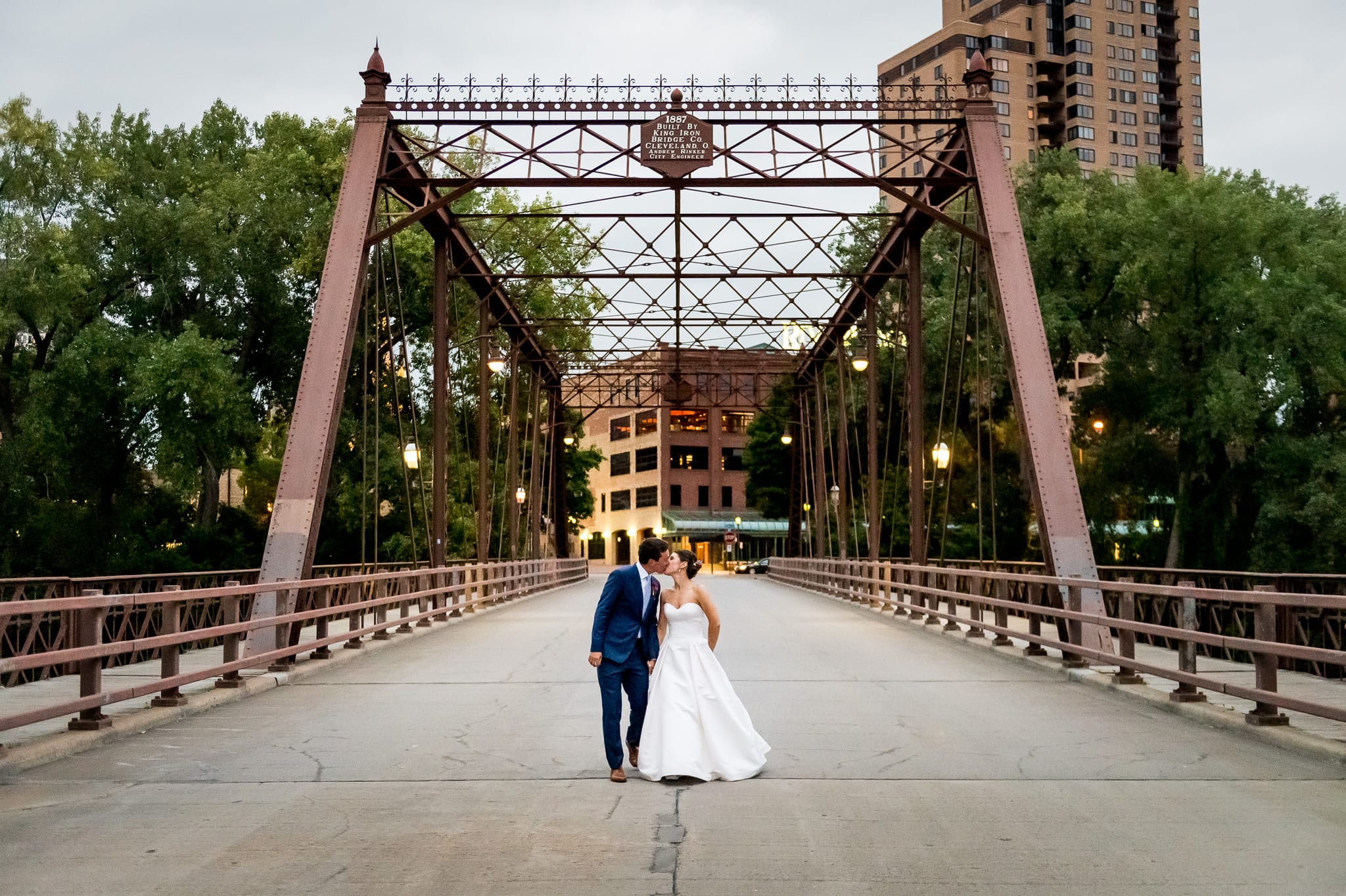 Bride and groom kissing in perfect symmetry on the Merriam Street Bridge in Minneapolis
