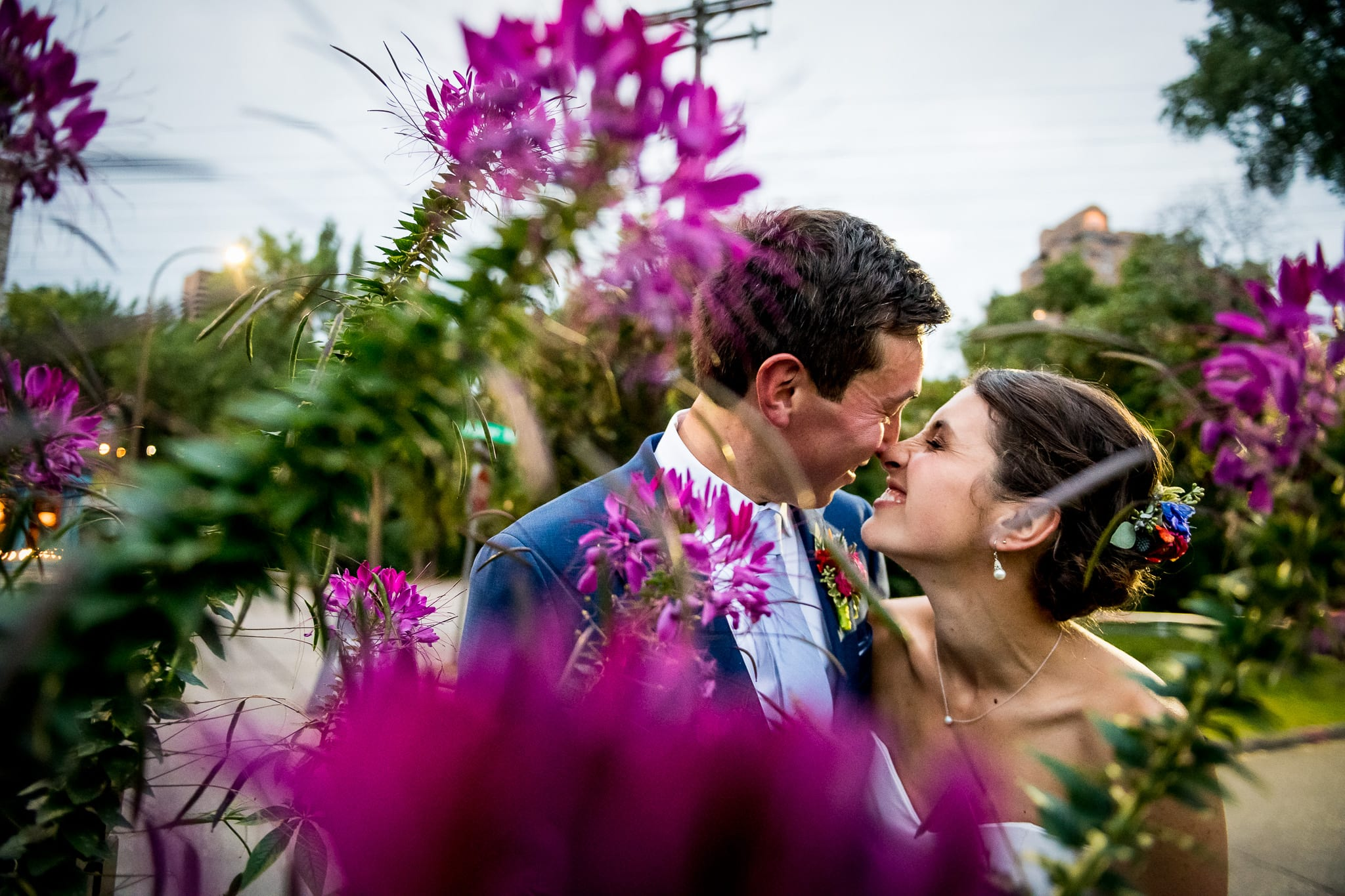 Bride and groom eskimo kissing shot thru some cool looking pink and green flowers in front of the Nicollet Island Pavilion