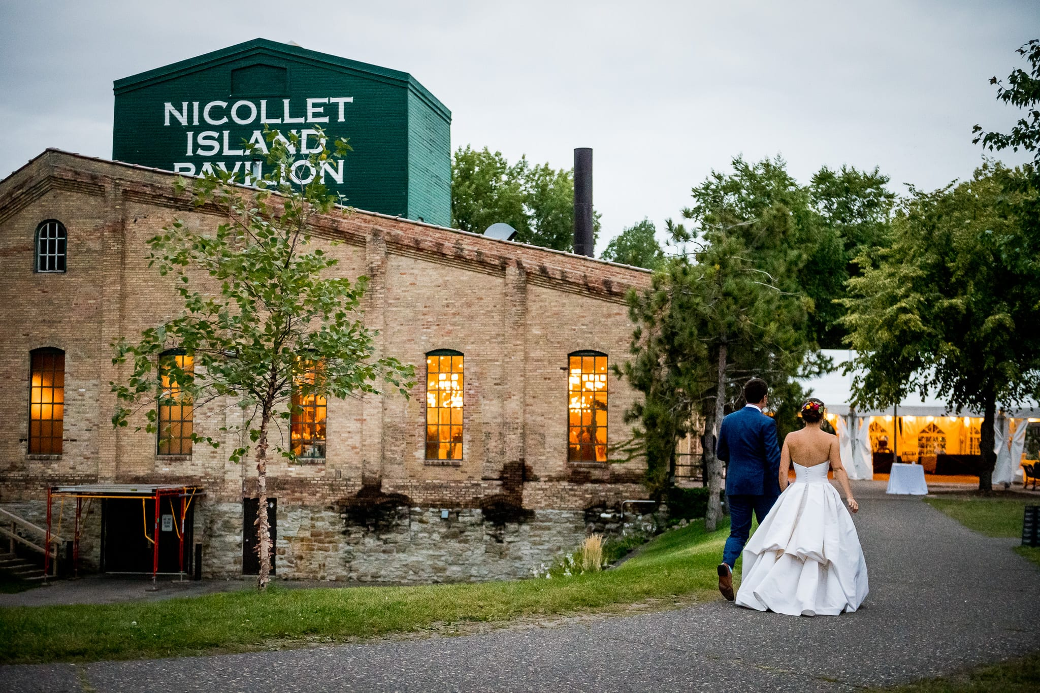 Exterior shot of the Nicollet Island Pavilion during a summer wedding with the bride and groom walking along the path