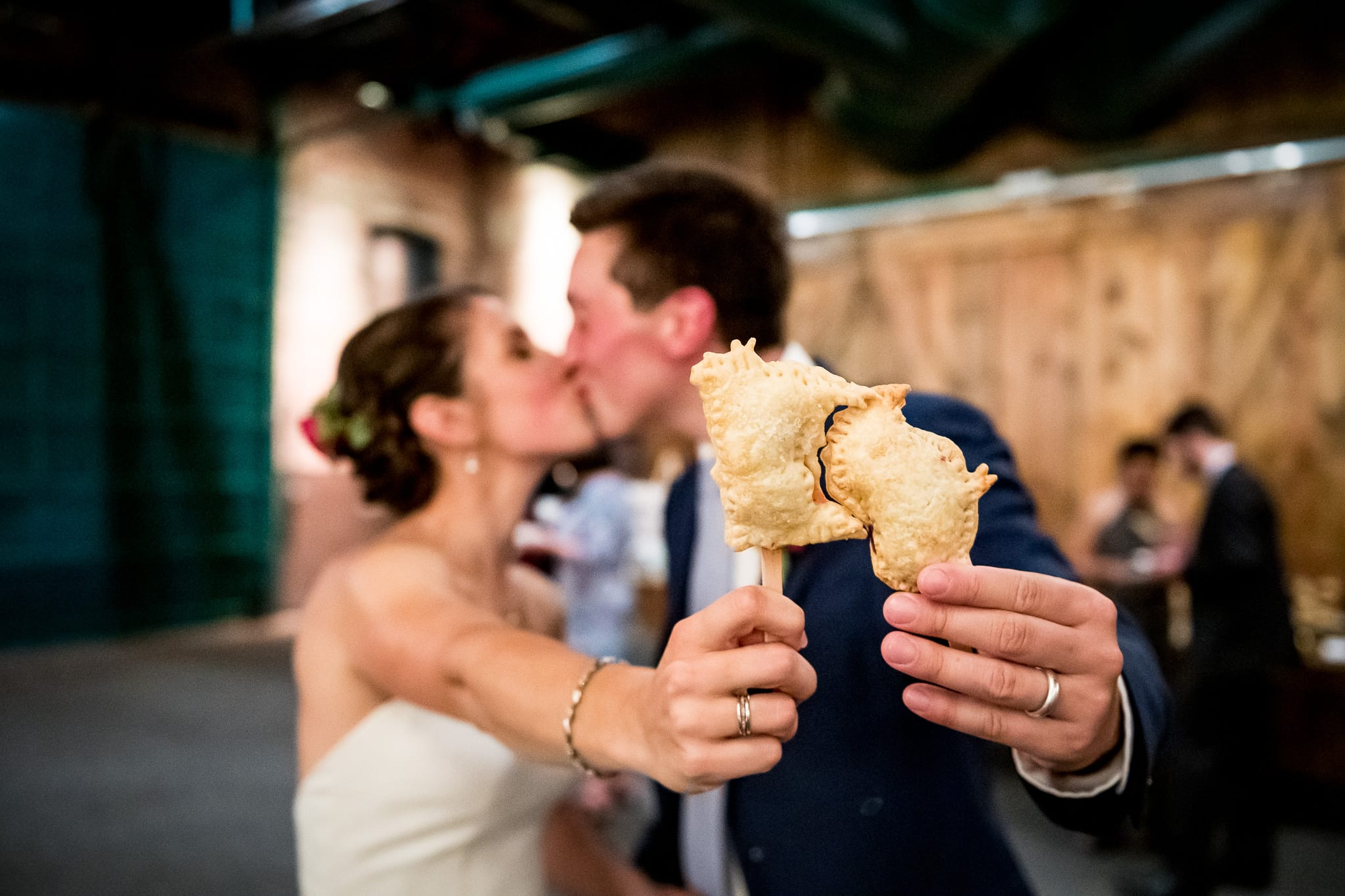 Bride holds her Minnesota shaped pop tart on a stick up to her grooms which is shape like Wisconsin, where they are both from respectively