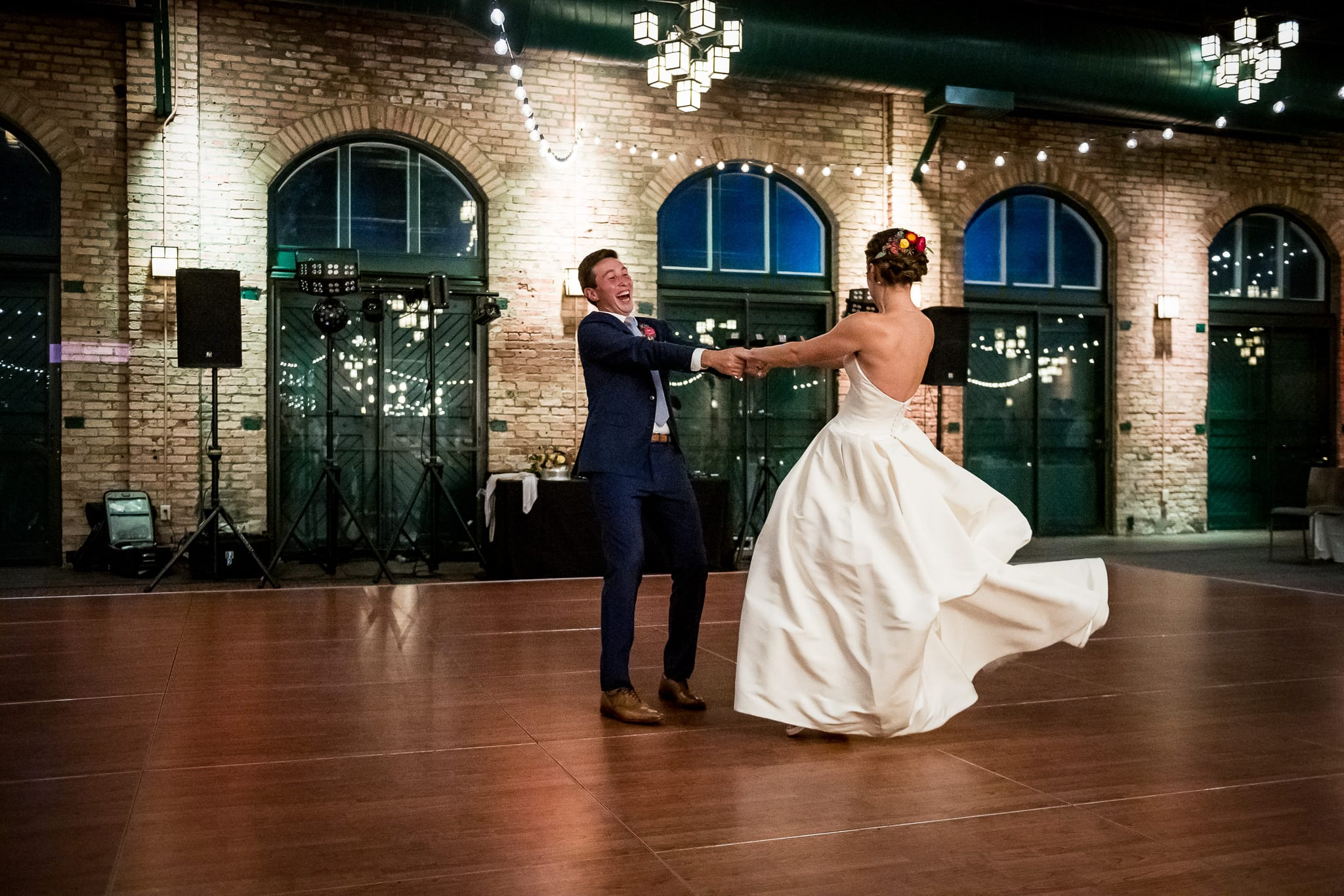 Groom swings his bride around on the dance floor