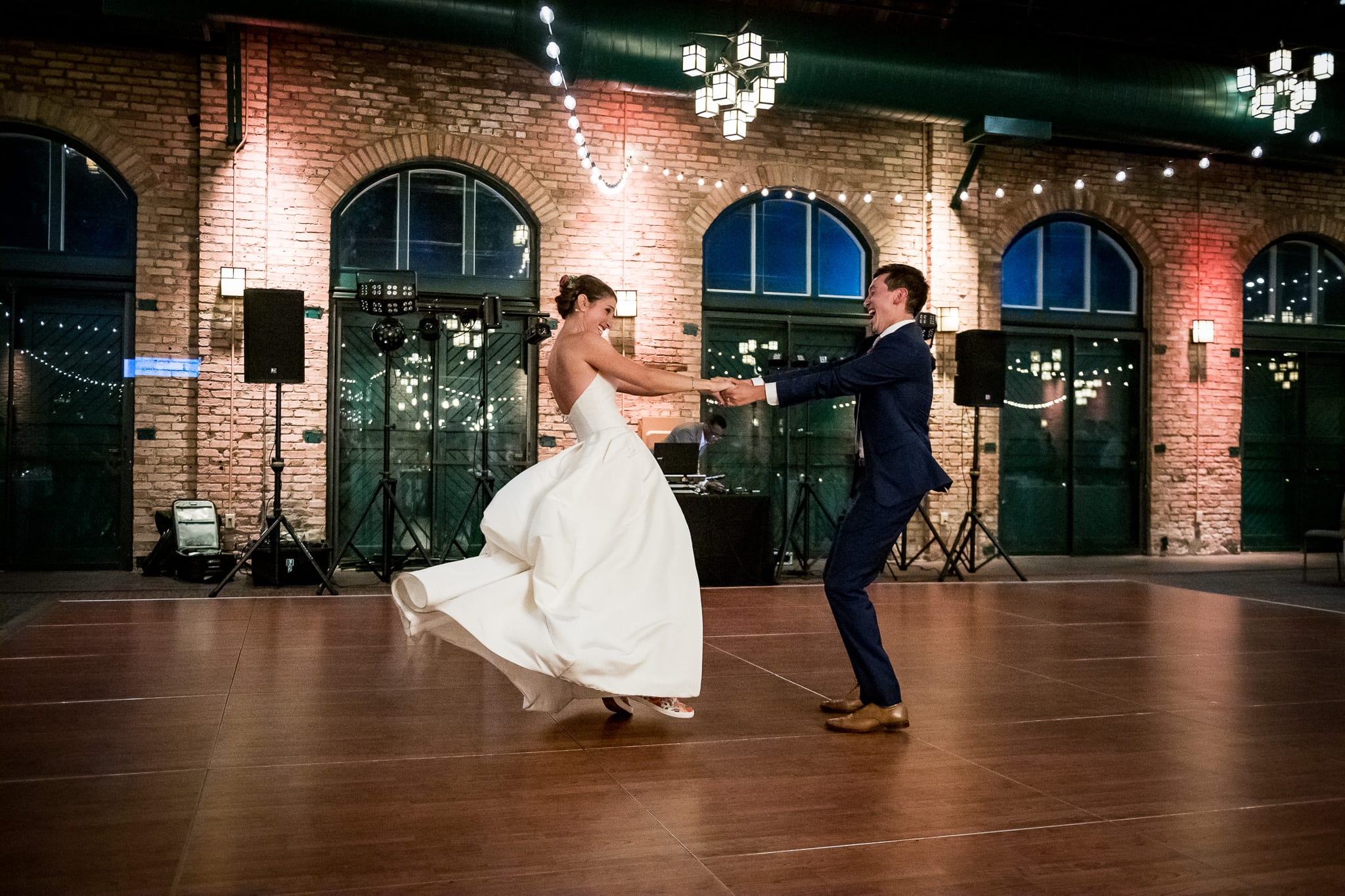 Bride and groom laughing out loud as they twirl each other around during their first dance at Nicollet Island Pavilion