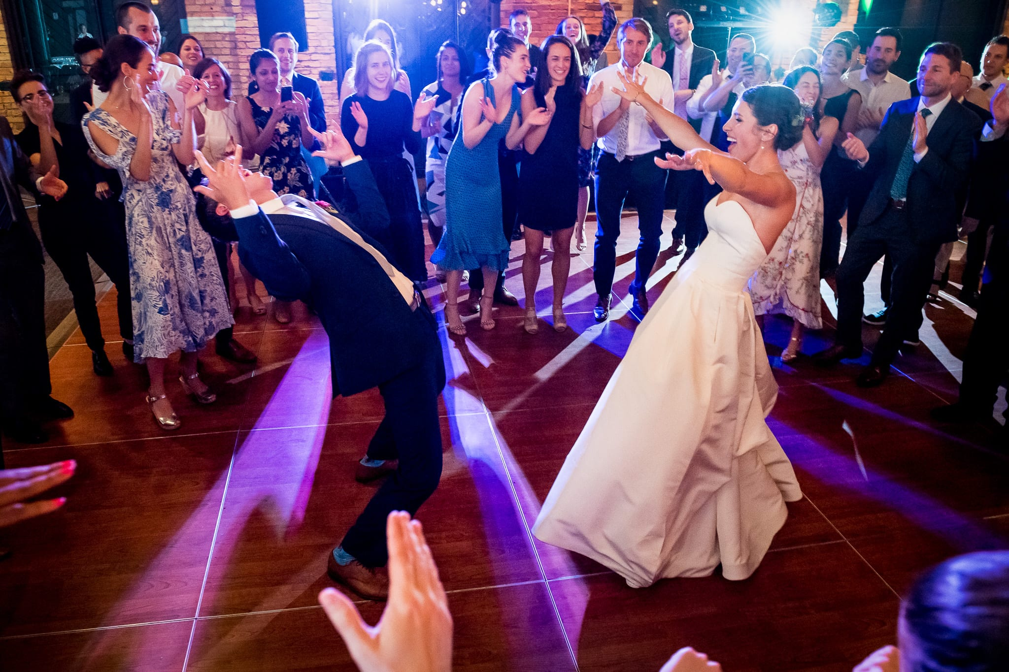 Groom bent all the way back and his bride raises her hands high as they dazzle their wedding guests on the dance floor