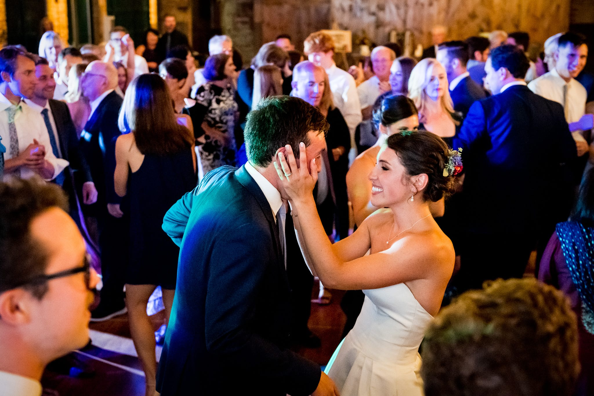 Bride squeezes her grooms face as they dance during their wedding