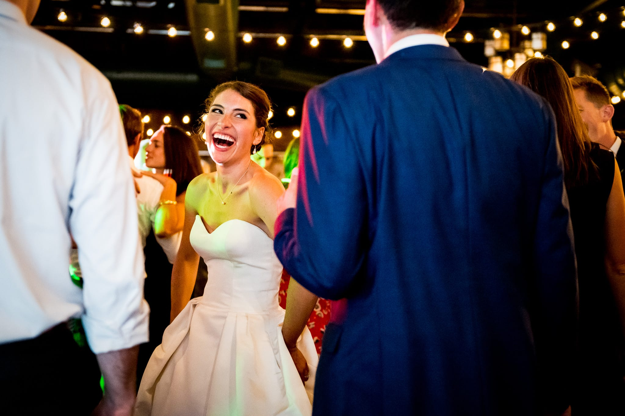 Bride shows of hug smile towards her new husband on the dance floor during their wedding