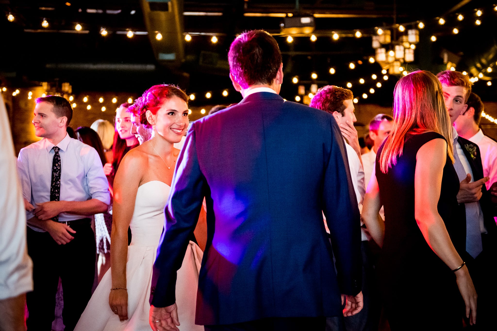 Bride looks intently at her groom on the dance floor with pink DJ lights shining brightly
