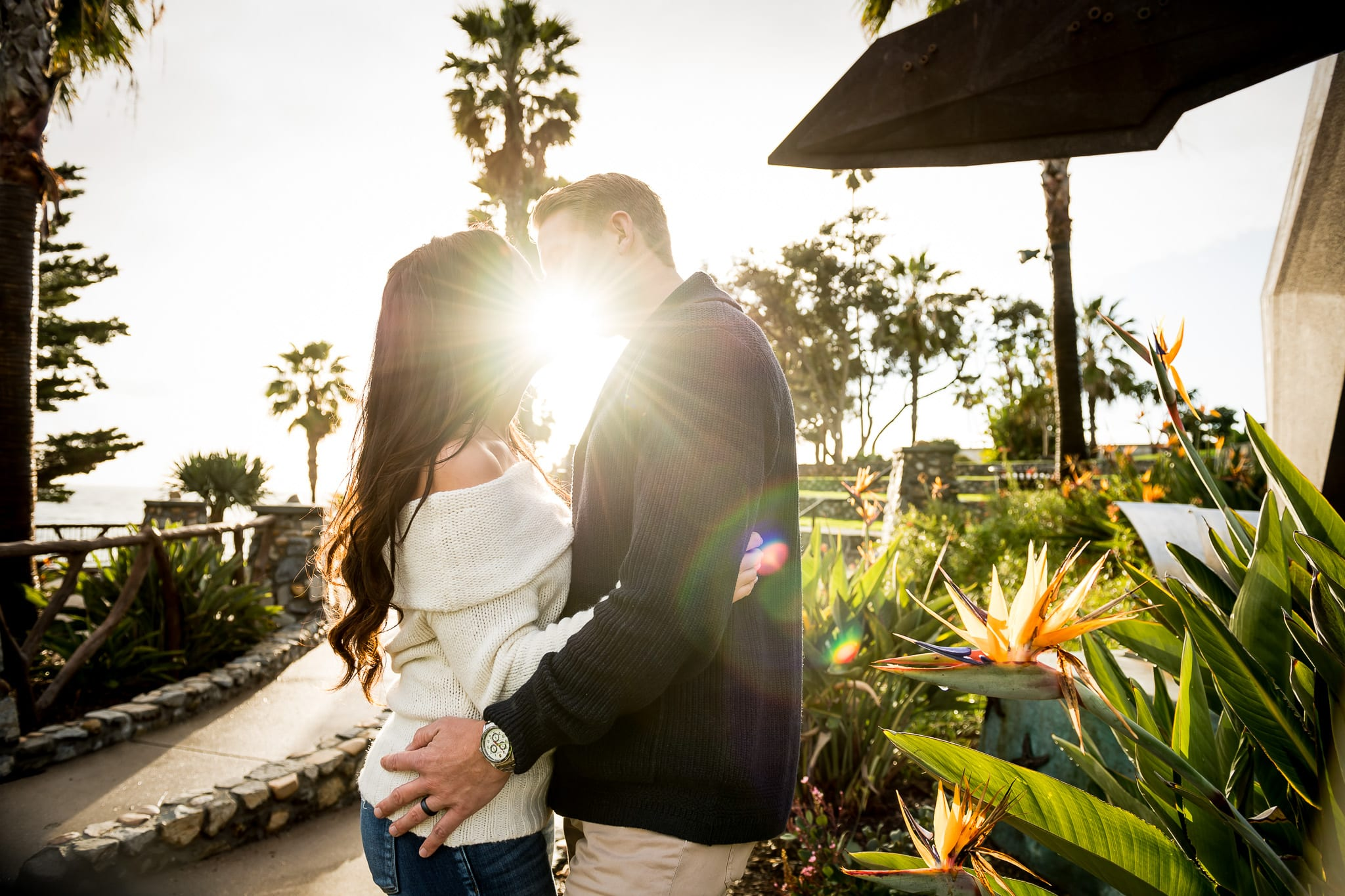 The moment right before a couple shares a sweet kiss at Heisler Park in Laguna Beach during their engagement session with the sun flaring perfectly in between their lips while they stand next to a beautiful bird of paradise flower