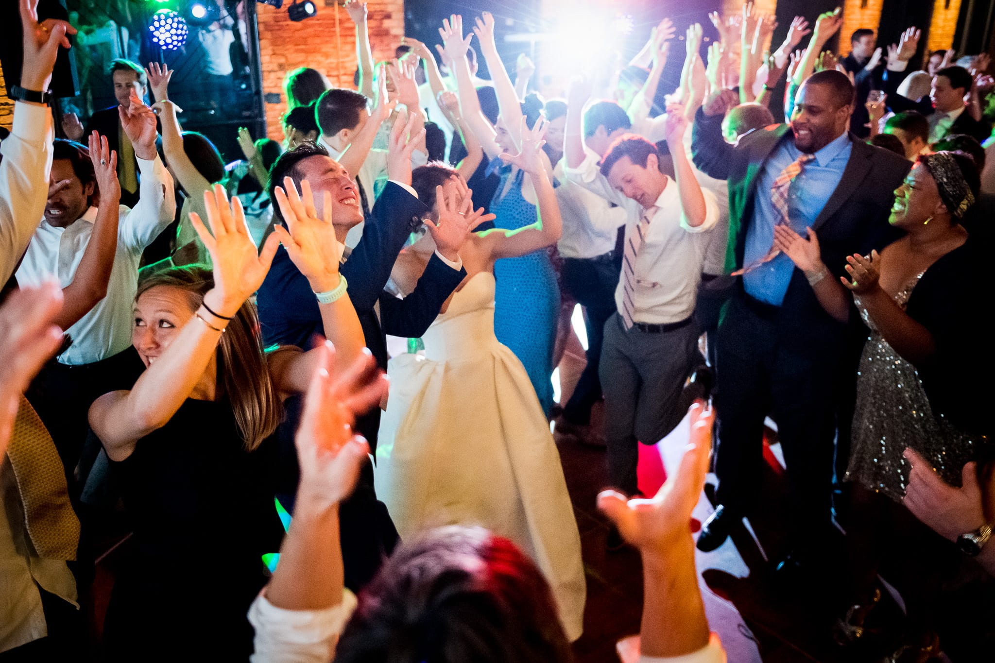 Jam packed dance floor with all of the wedding guests with their hands in the air during a Nicollet Island Pavilion wedding