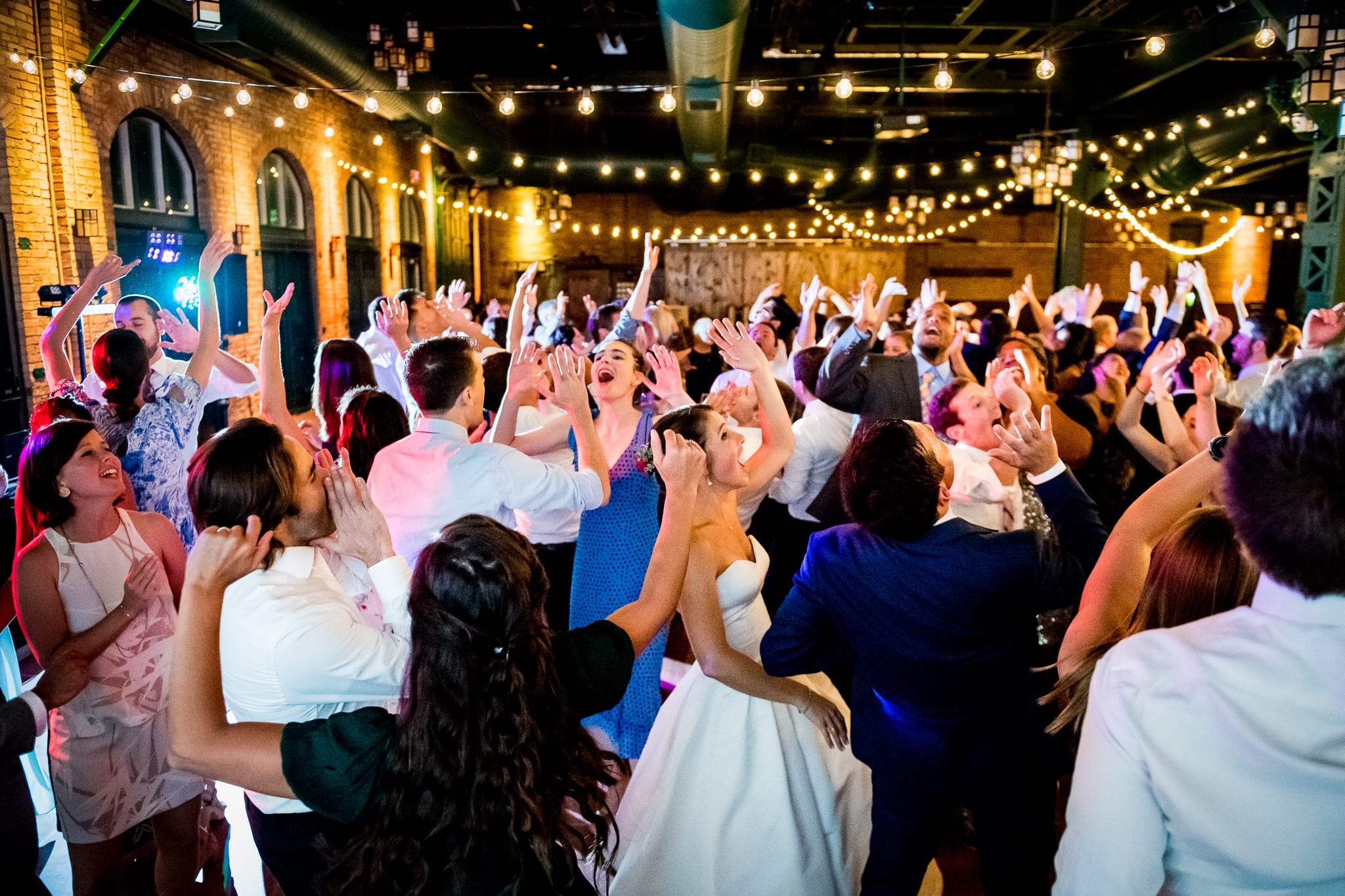 Wide view showing the indoor space of the Nicollet Island Pavilion with a packed dance floor all the wedding guests hands in the air
