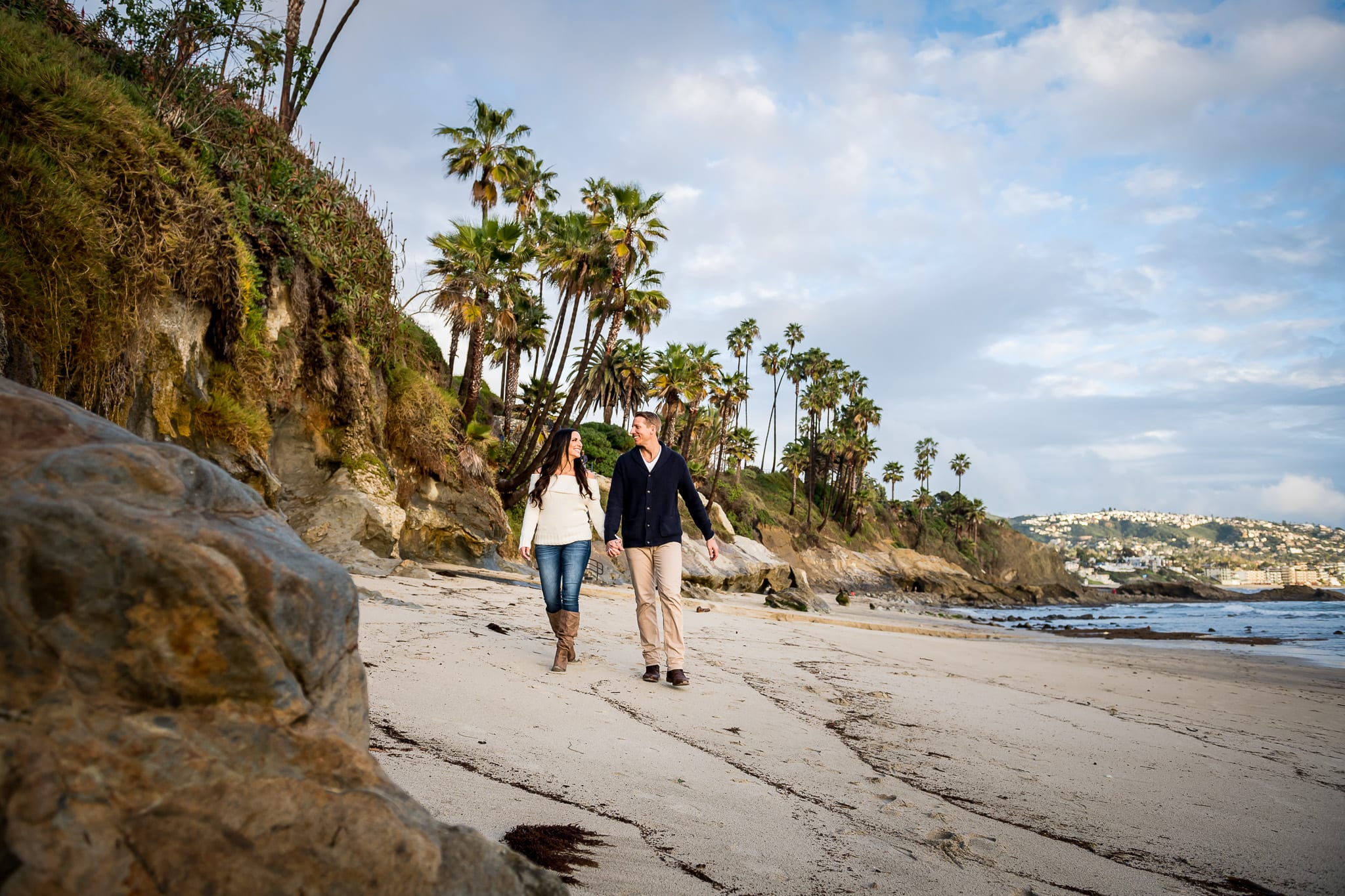 Low angle view of couple holding hands and walking along the beach, in between the small rocky cliffs and the ocean waves, while shooting their engagement session in Laguna Beach, at Picnic Cove