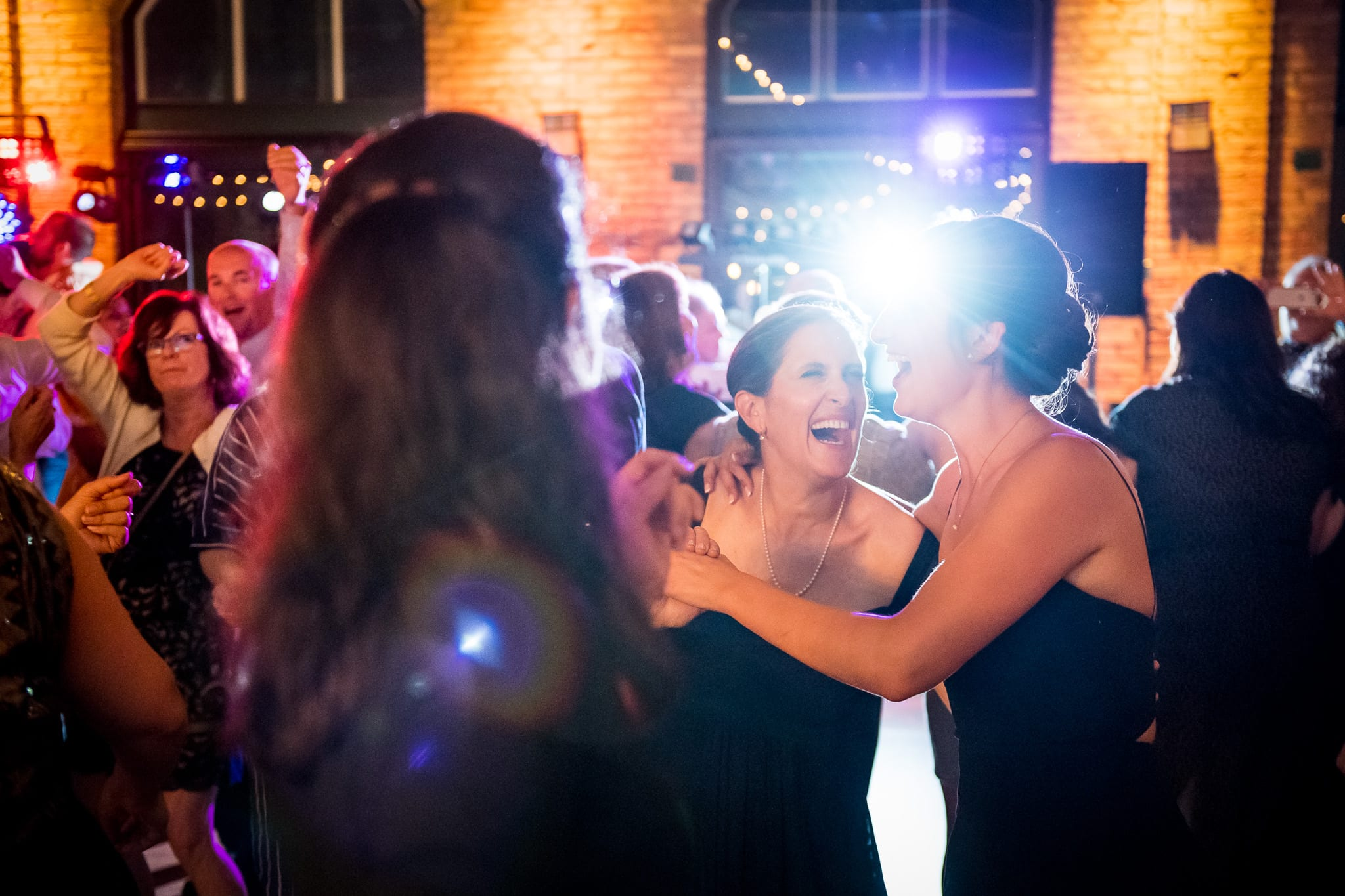 Mother and daughter laughing with a flare of light popping in between them on the dance floor