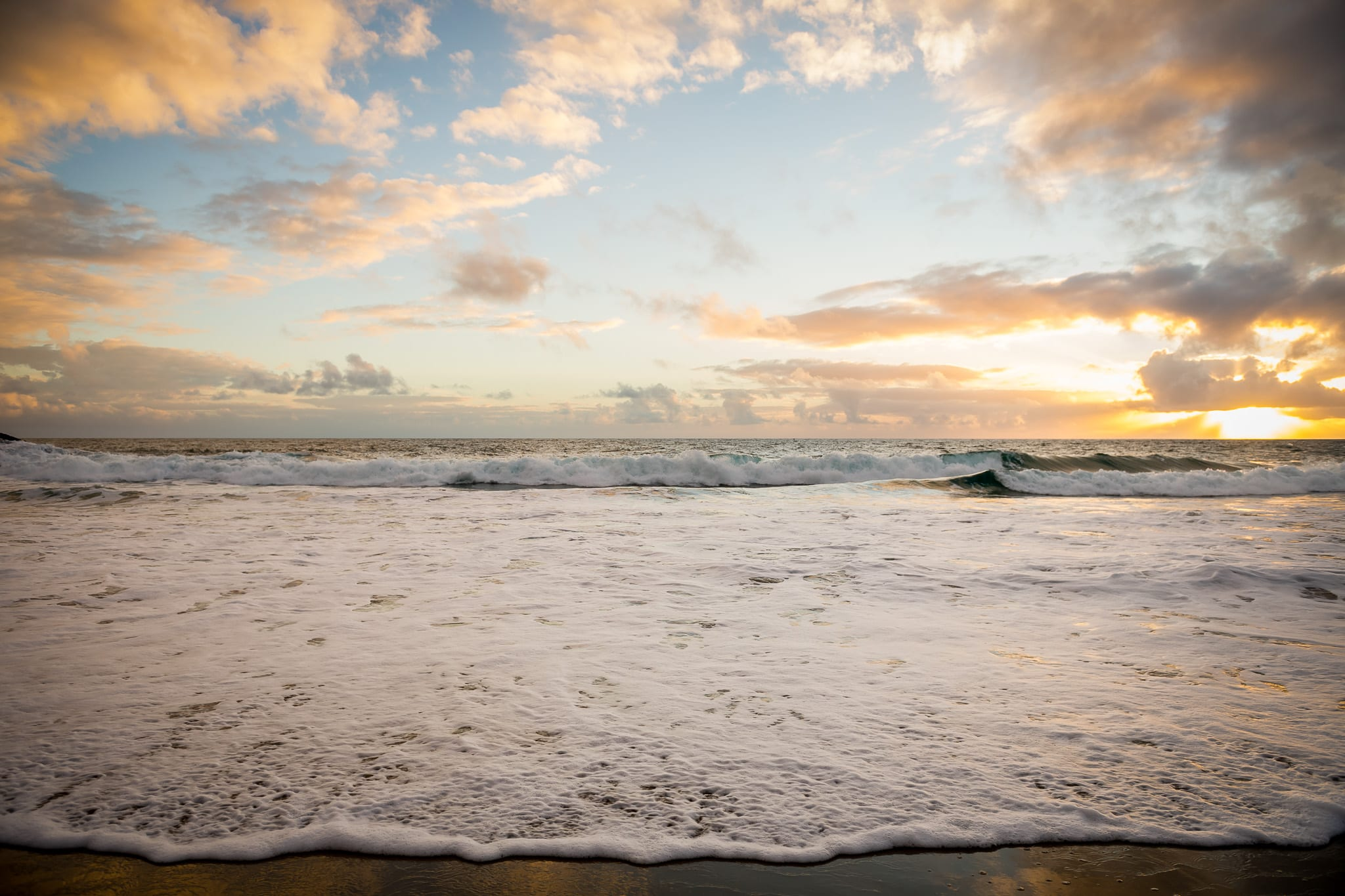 Sunset facing the Pacific Ocean from Aliso Beach in Laguna Beach, California with a colorful skies and long waves crashing in the foreground