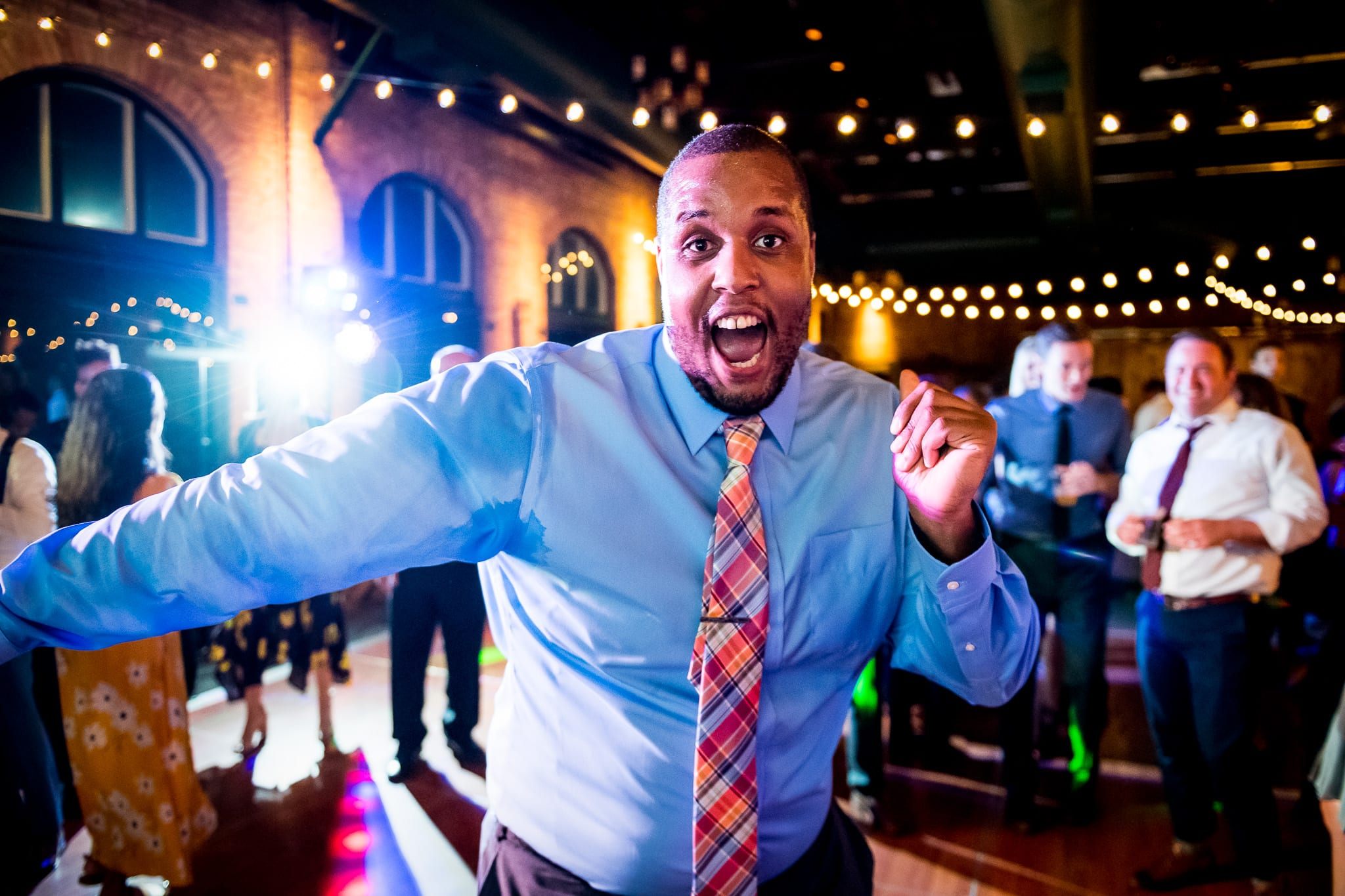 Happy and sweaty wedding guest dances and poses for a wide open smile on the middle of the dance floor