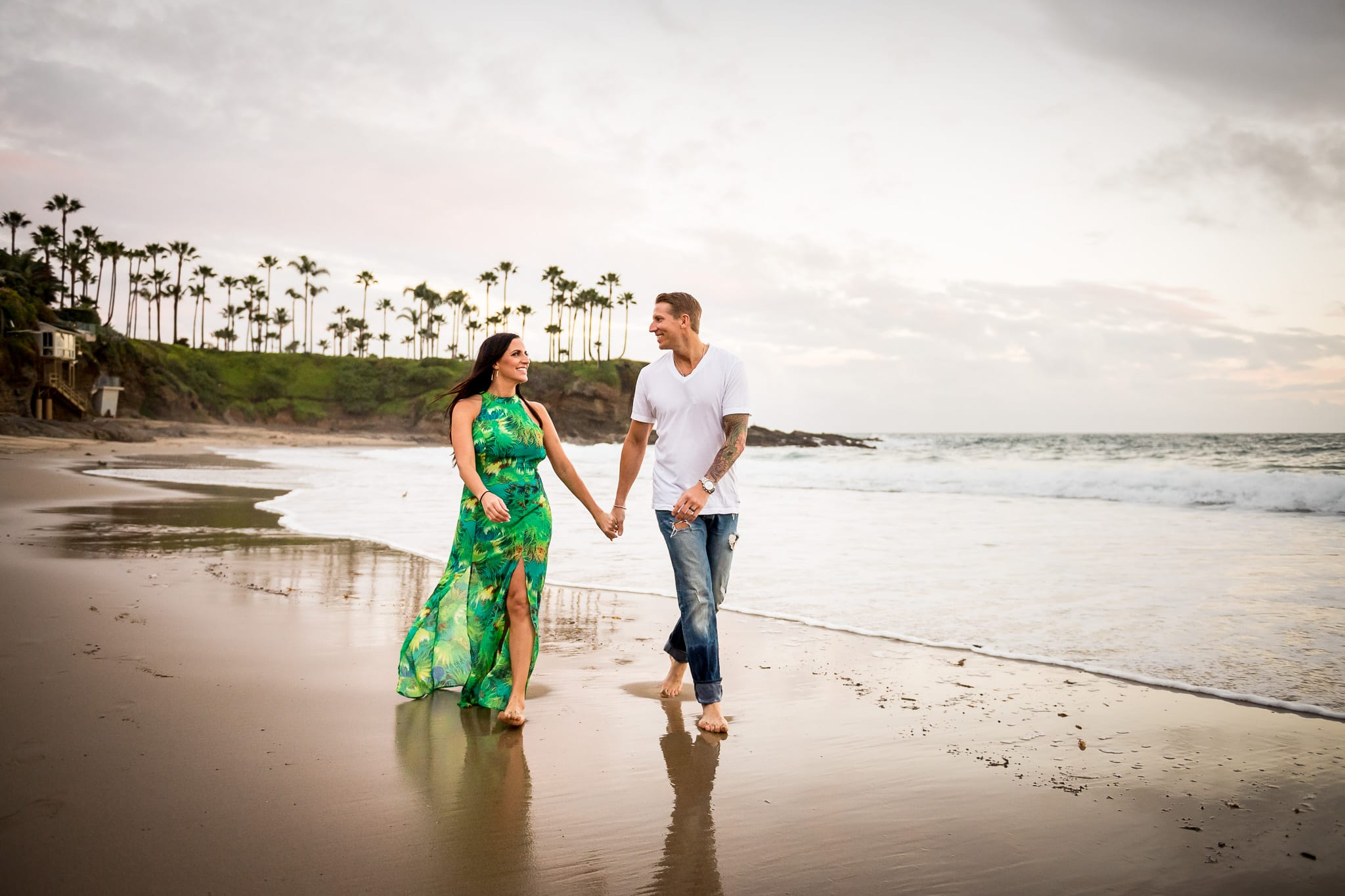 Newly engaged couple holding hands, smiling at each other, and walking barefoot on the sandy beach at Crescent Bay Beach in Laguna Beach, California. The women is in a colorful floral printed green dress and the man is wearing a white t-shirt with one arm adorned with a tattoo sleeve