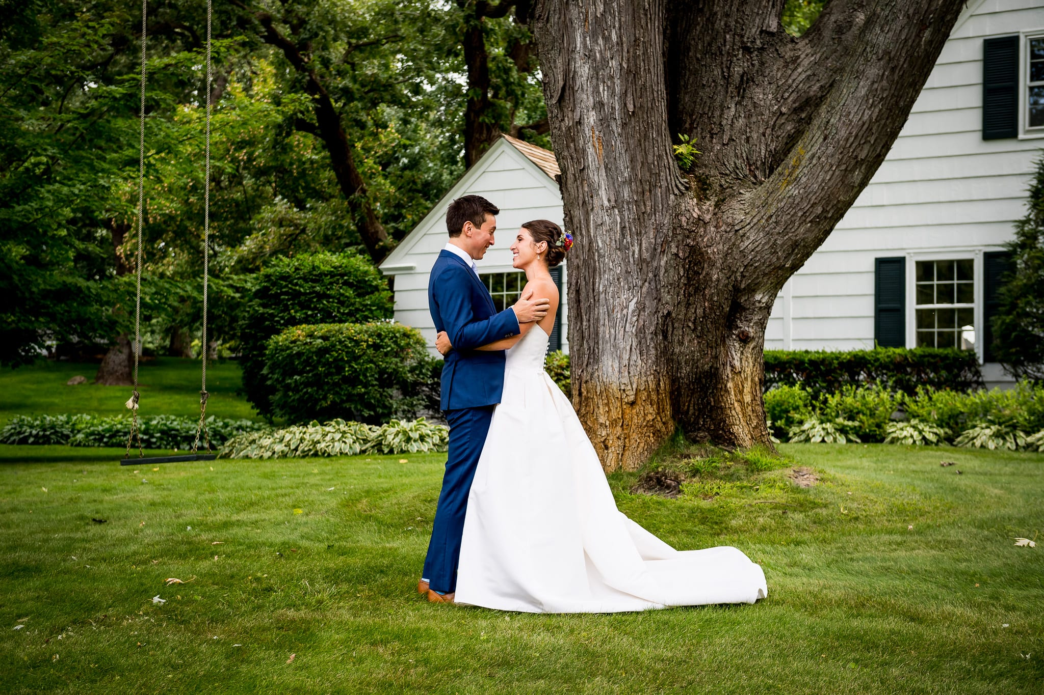 Bride and groom see each other for the first time on their wedding day on a lush green lawn, in front of a large tree and tree swing