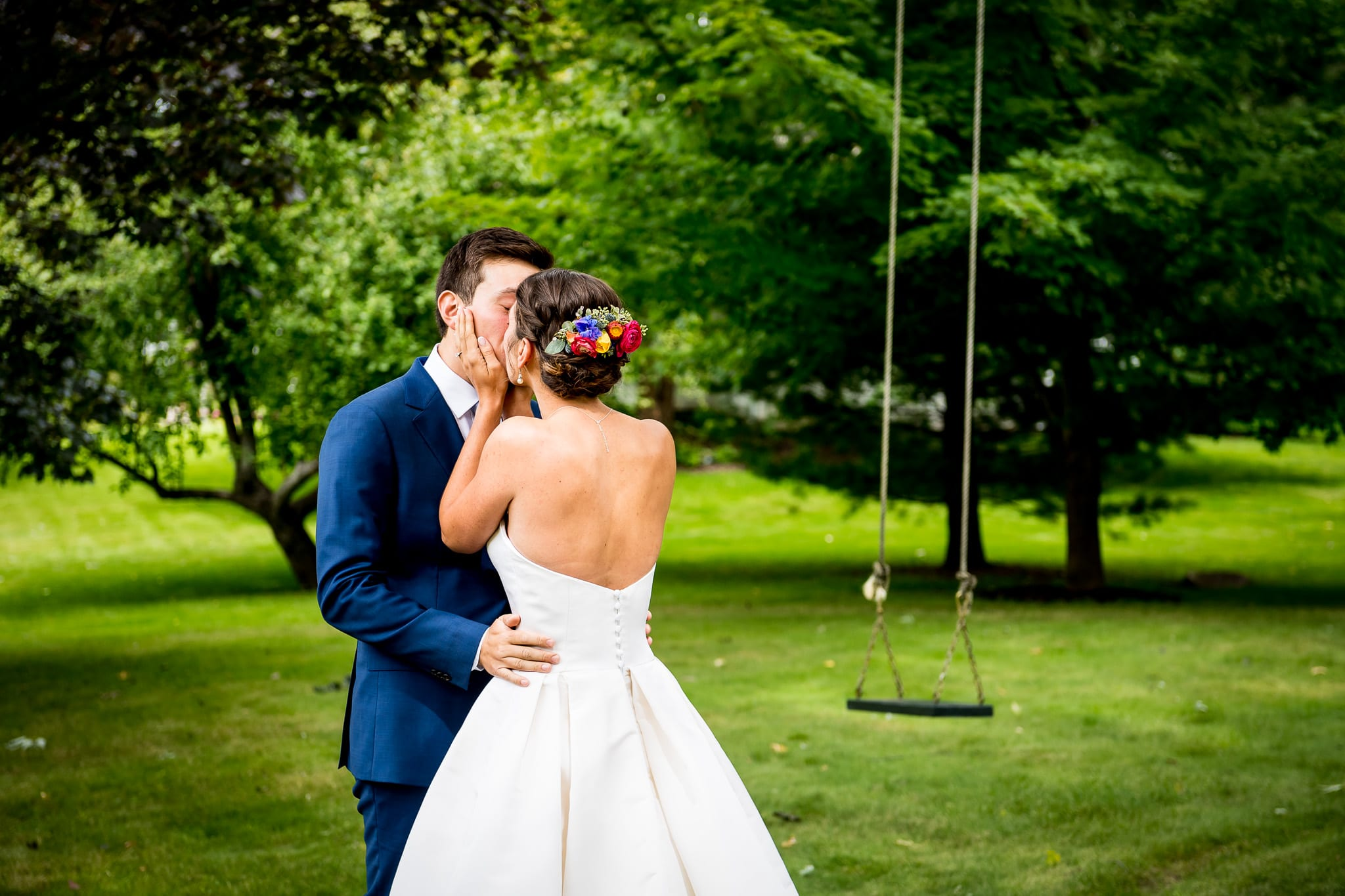 Bride and groom kiss by tree swing