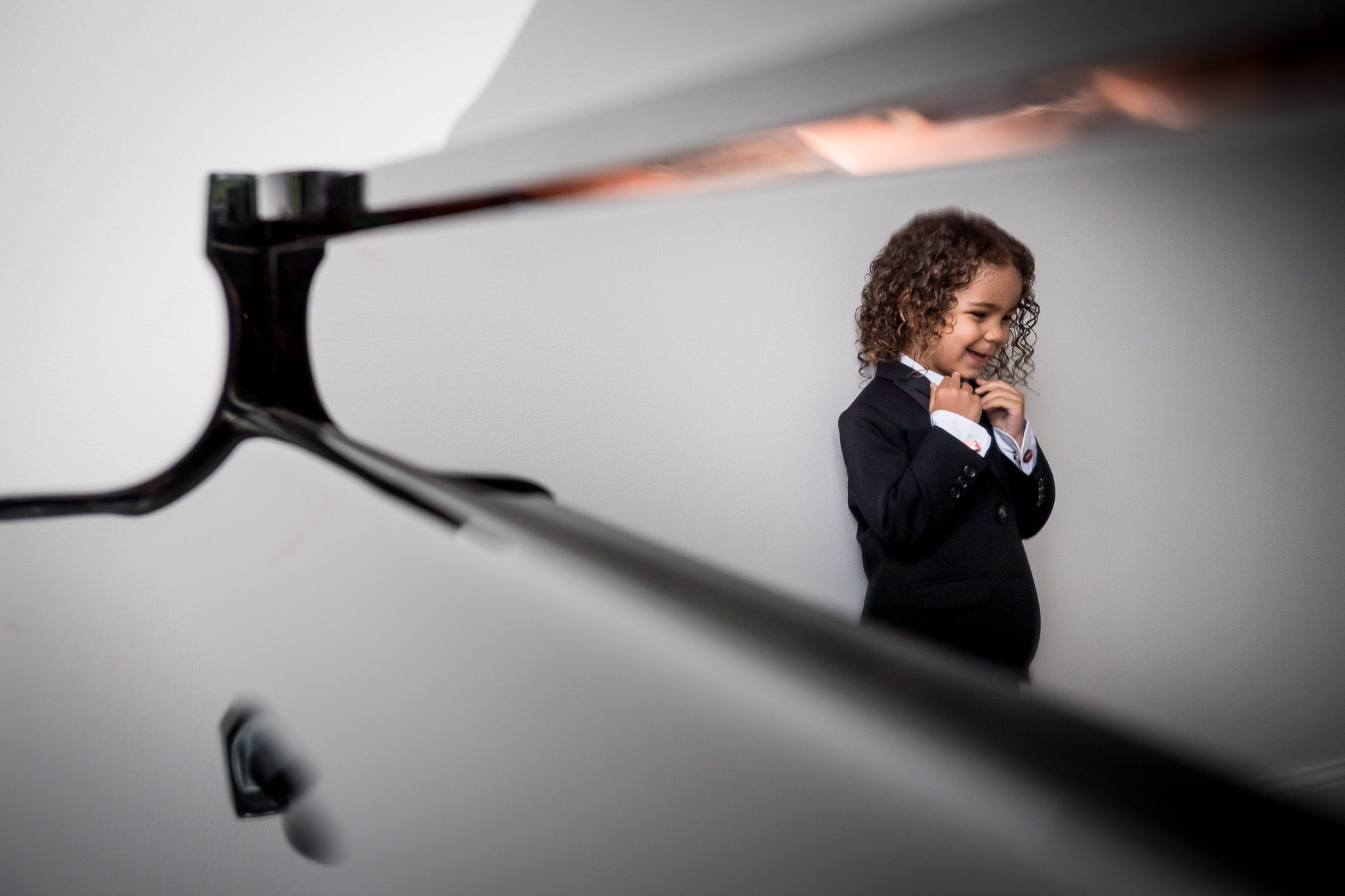 Image of the bride and groom's young son in his tuxedo reflecting the surface of a black grand piano.