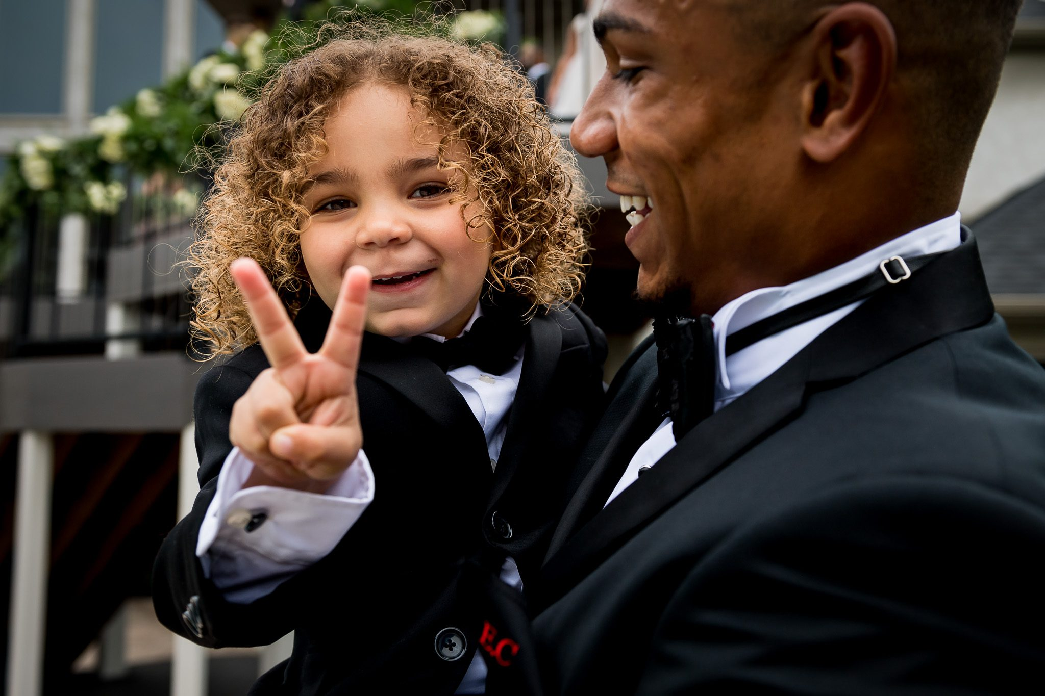 3-year-old throwing up a peace sign with his fingers, while smiling, and wearing an amazing suit, and in his dad arms, who just got married.