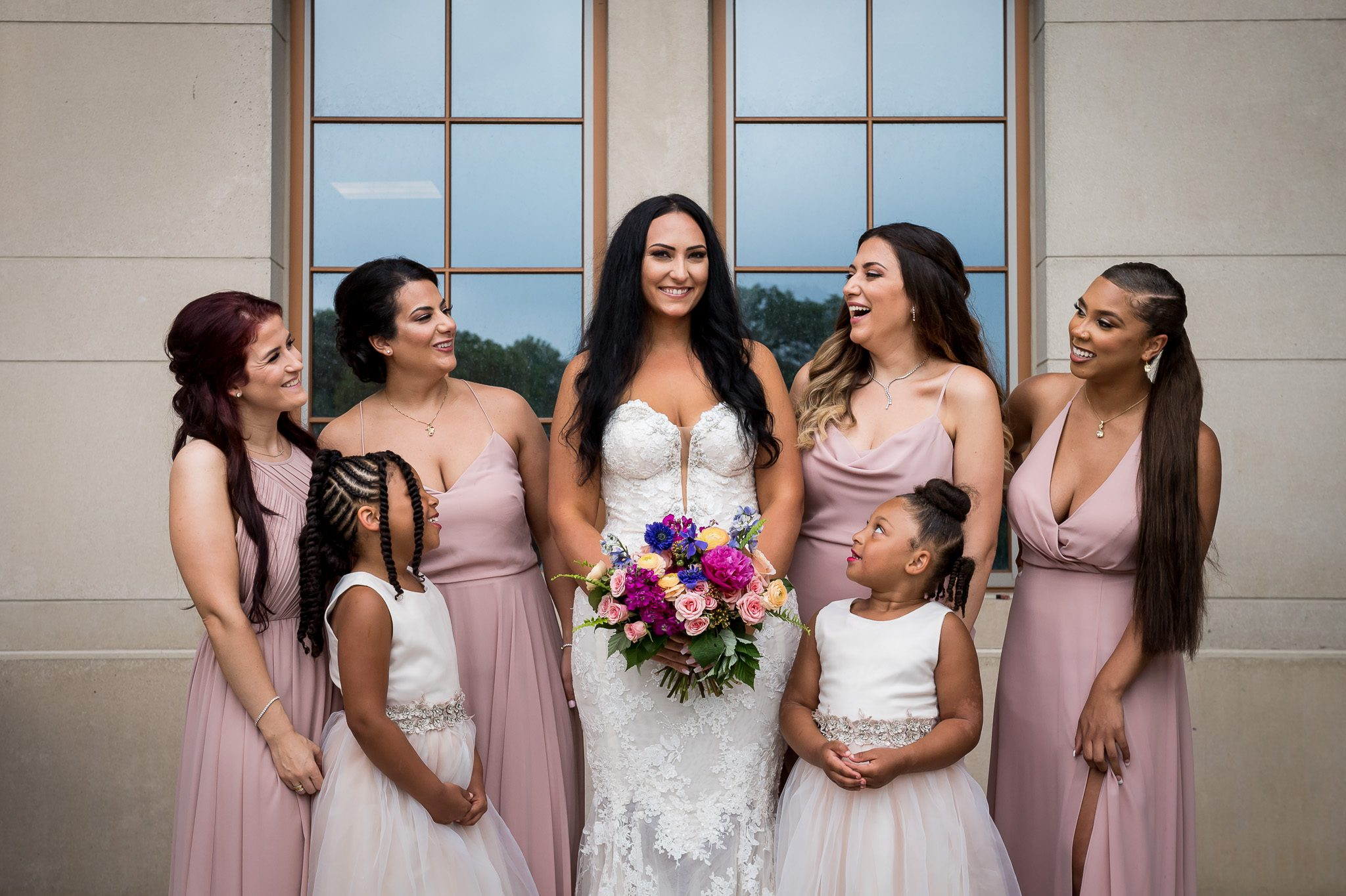 Bridesmaids pose together and laugh together during a beautiful backyard wedding in MN.