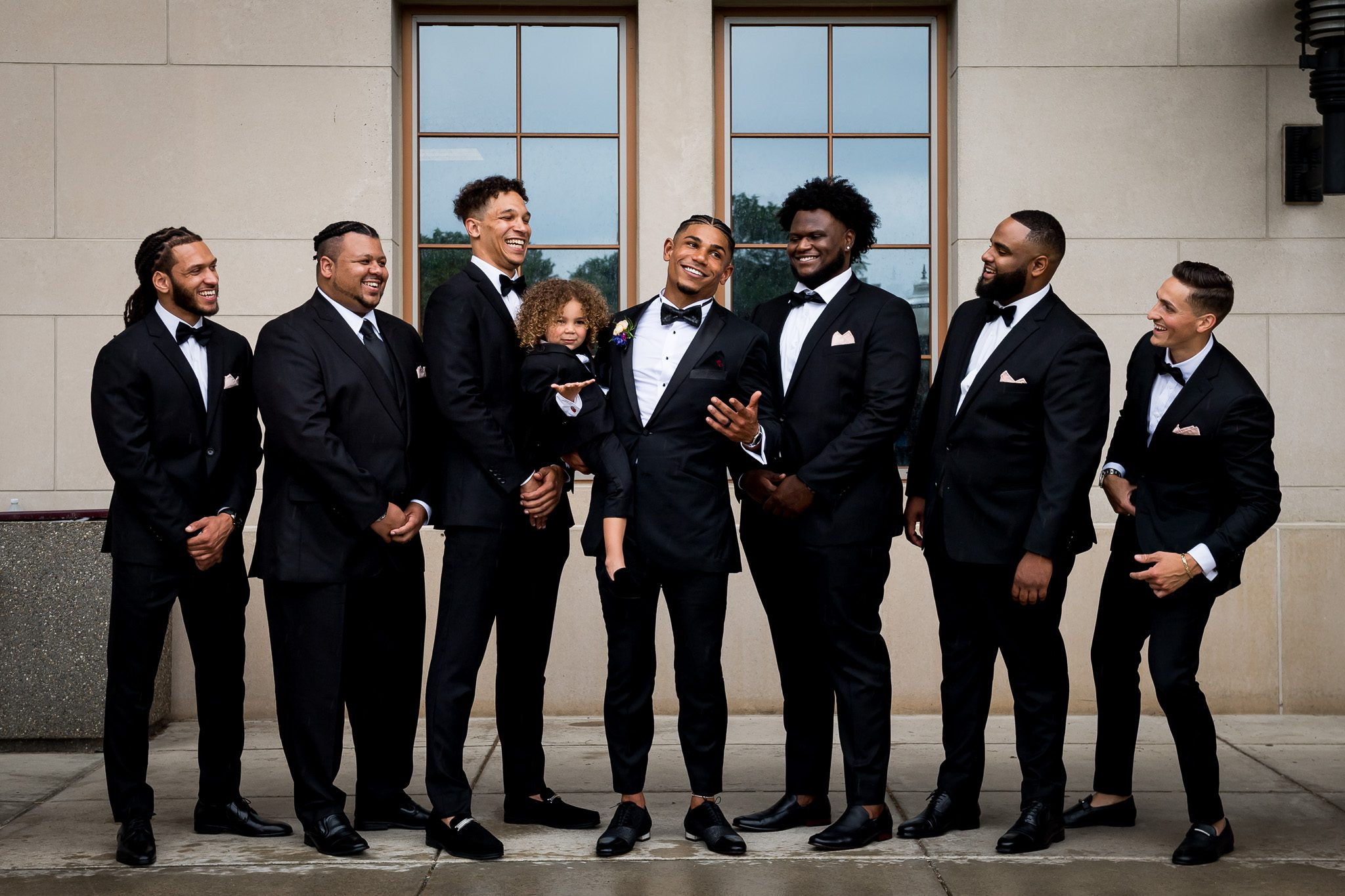 Groomsmen pose together and laugh during a photo stop before returning to their backyard wedding reception.