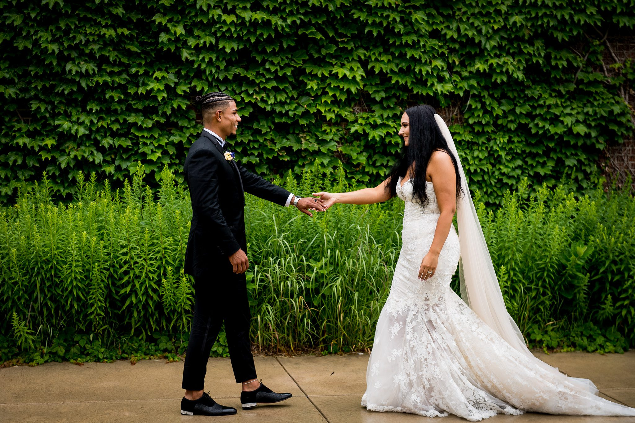 Bride & Groom reach their hands out to each other in front of a lush ivy covered wall.