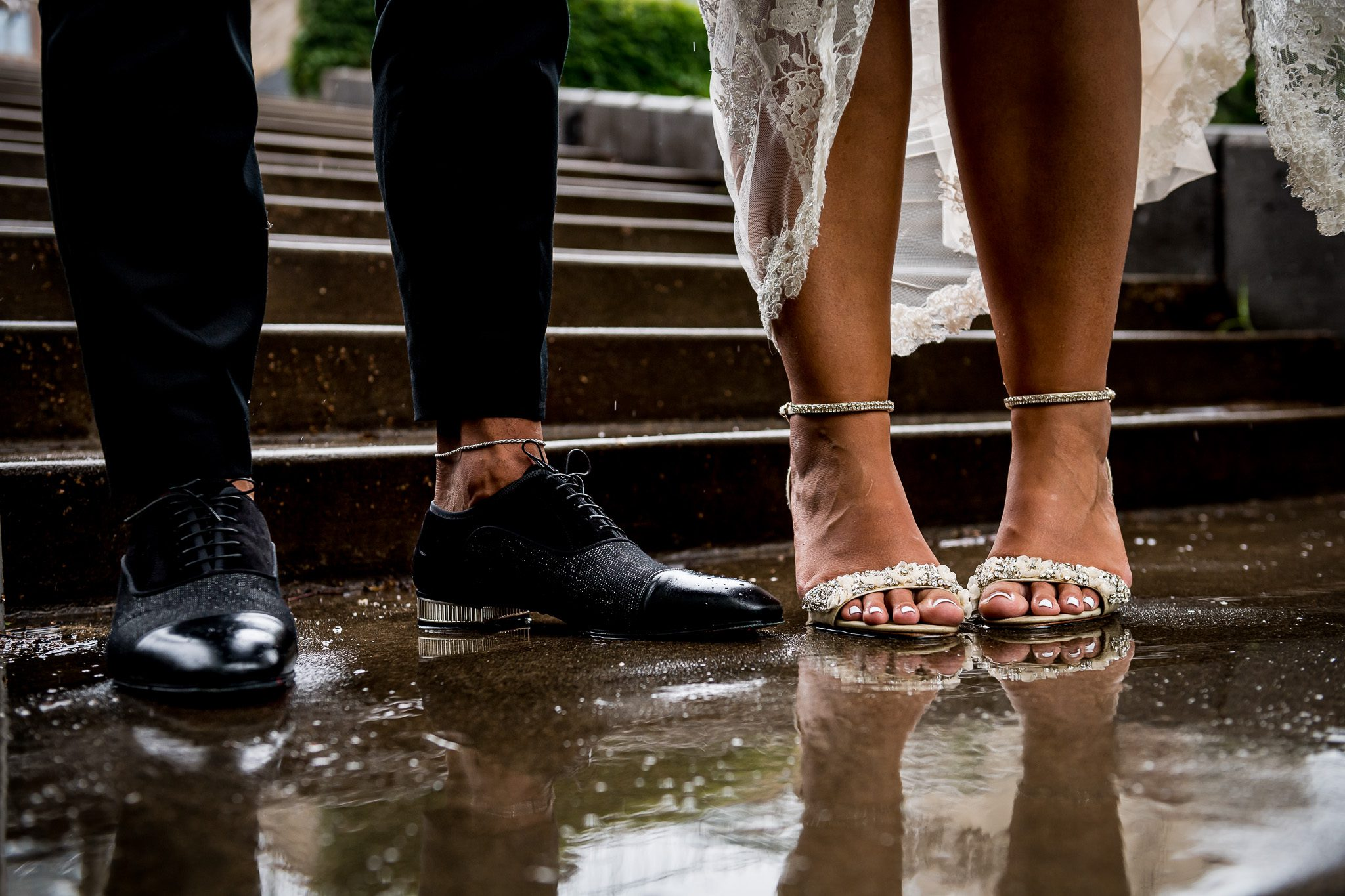 Bride and Groom's shoes reflecting in a rain puddle on the day of their rainy backyard wedding in Minnesota