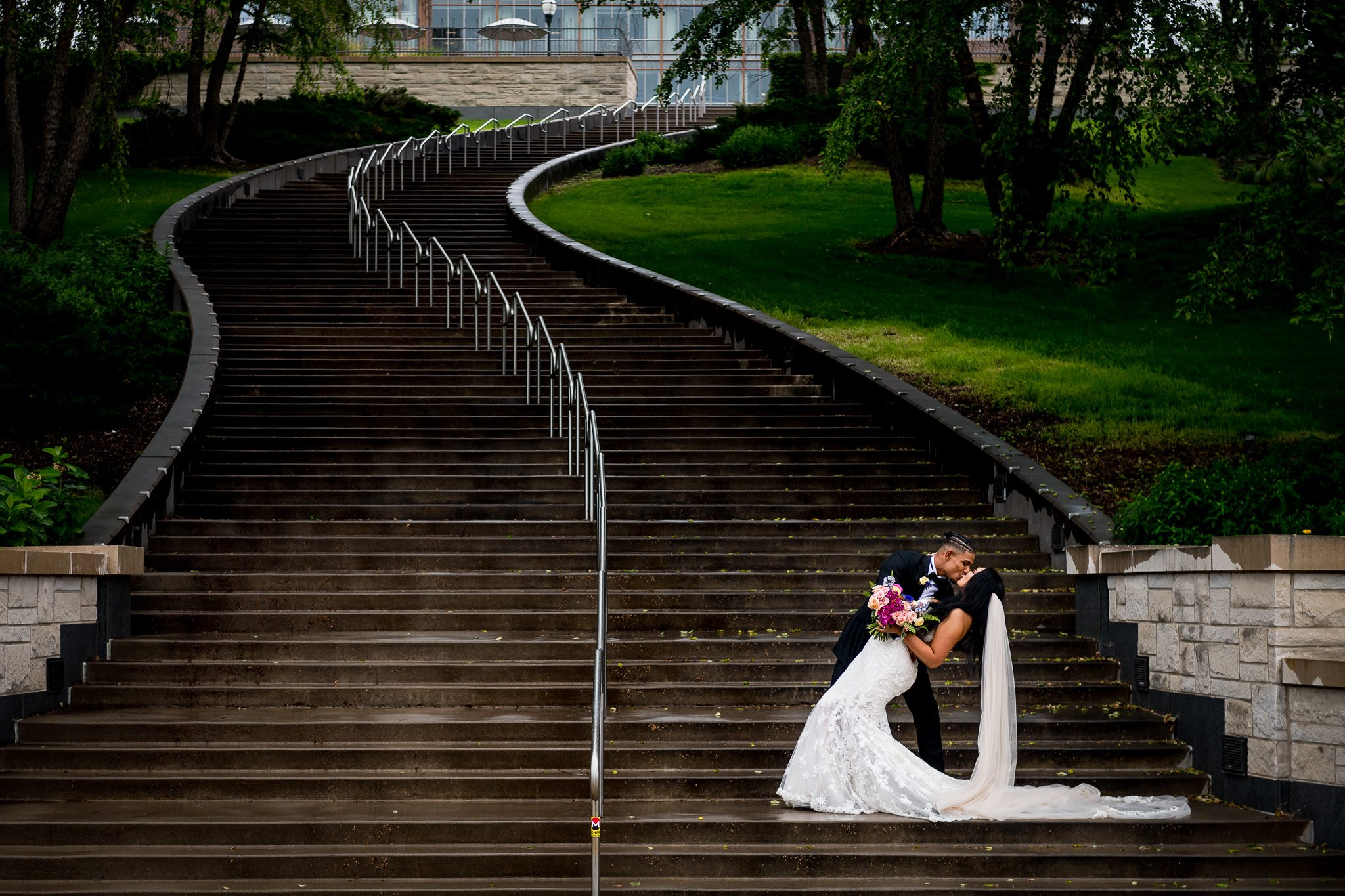 Elijah Campbell (nfl player for the Miami Dolphins) dips his bride Anisse back and then leans in for a kiss at the bottom of a long and winding staircase at the University of Minnesota.