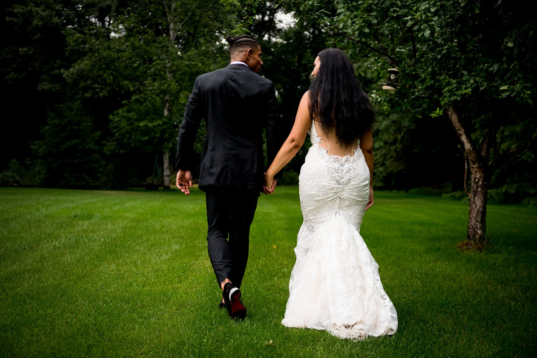 Elijah Campbell (nfl player) and his beautiful bride Anisse walking hand in hand, in the grass, under light rainfall, during their backyard wedding in Minnesota.