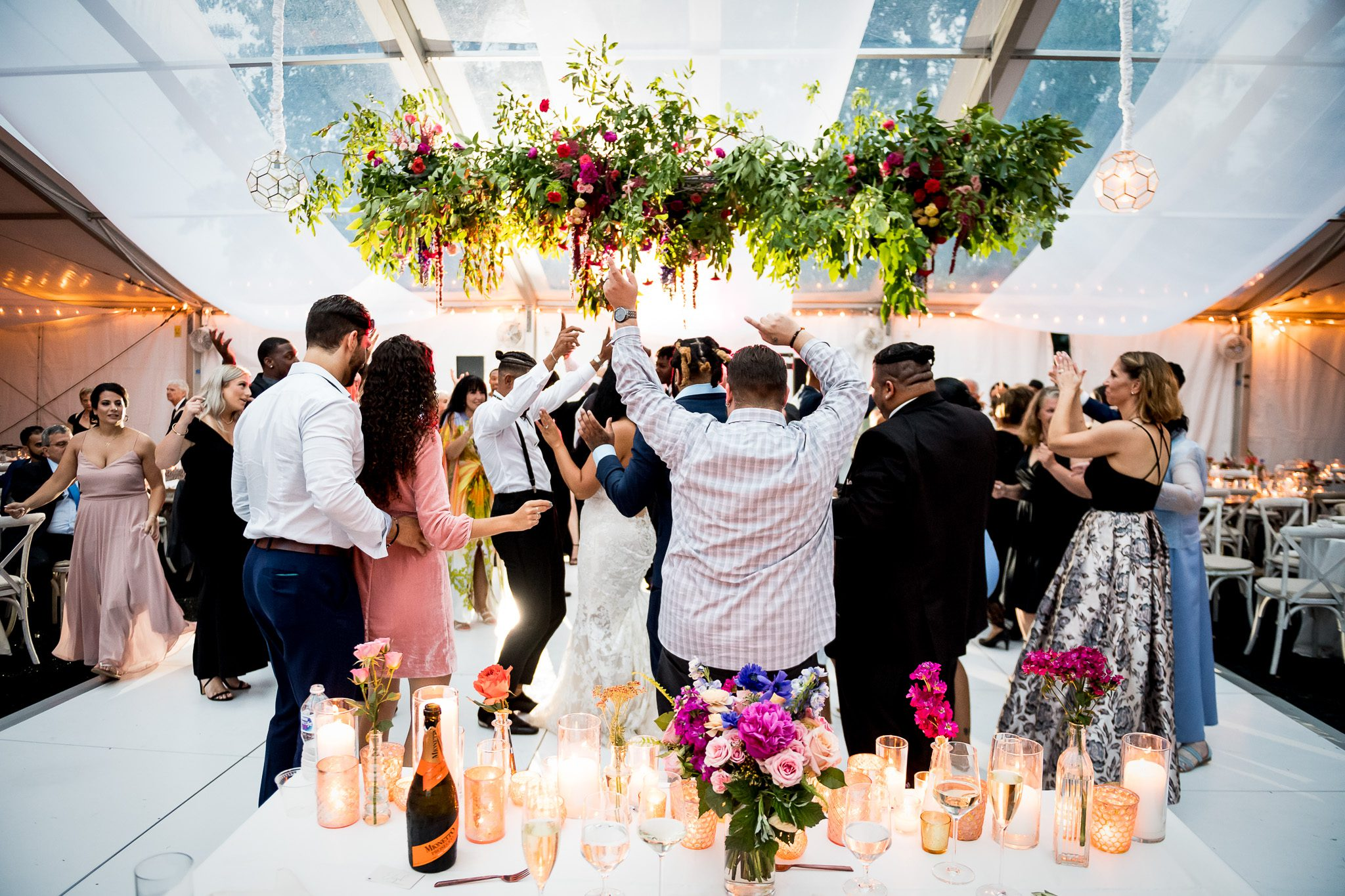 The dance floor is packed inside a florally decorated white tent at a Minnesota backyard wedding.